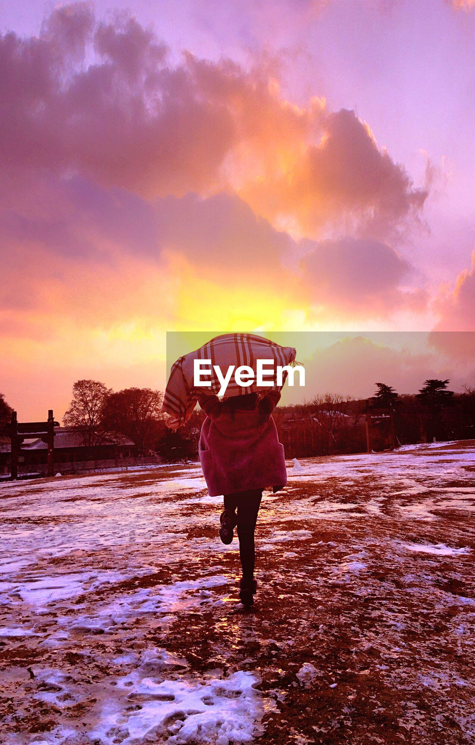 sunset, lifestyles, sky, leisure activity, rear view, water, full length, standing, cloud - sky, orange color, walking, men, season, weather, person, built structure, dusk, architecture