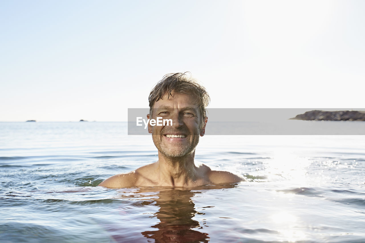 PORTRAIT OF SMILING YOUNG MAN AGAINST SEA