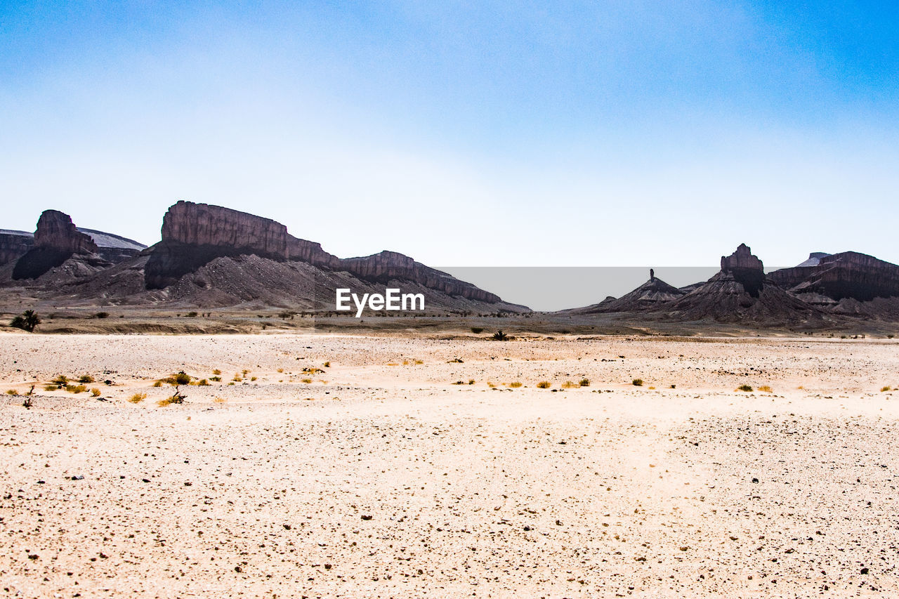 nature, tranquil scene, mountain, tranquility, geology, landscape, arid climate, beauty in nature, scenics, day, physical geography, rock - object, desert, outdoors, non-urban scene, clear sky, blue, no people, sky, mountain range, travel destinations