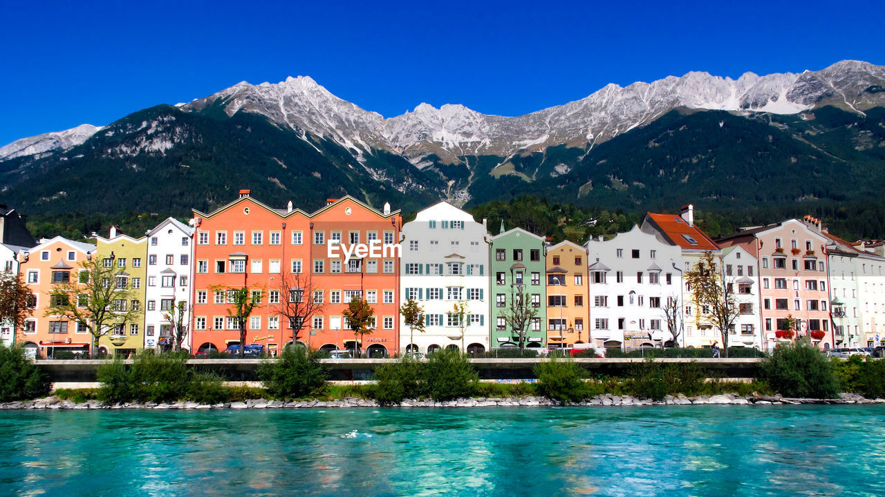 mountain, building exterior, architecture, water, built structure, sky, building, tree, residential district, nature, blue, scenics - nature, beauty in nature, no people, waterfront, plant, day, city, clear sky, mountain range, outdoors, turquoise colored, swimming pool