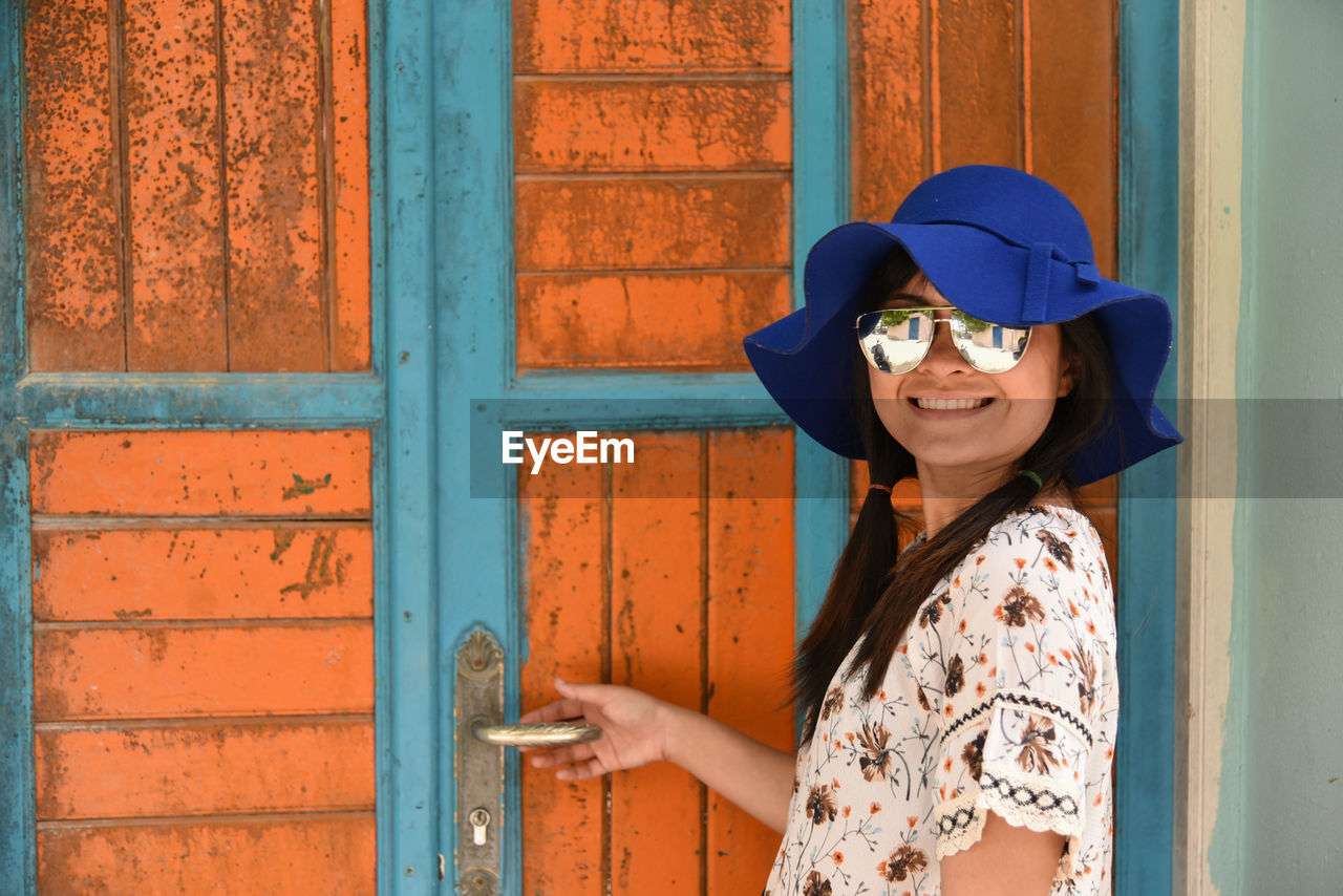 Portrait Of Smiling Young Woman Standing By Door
