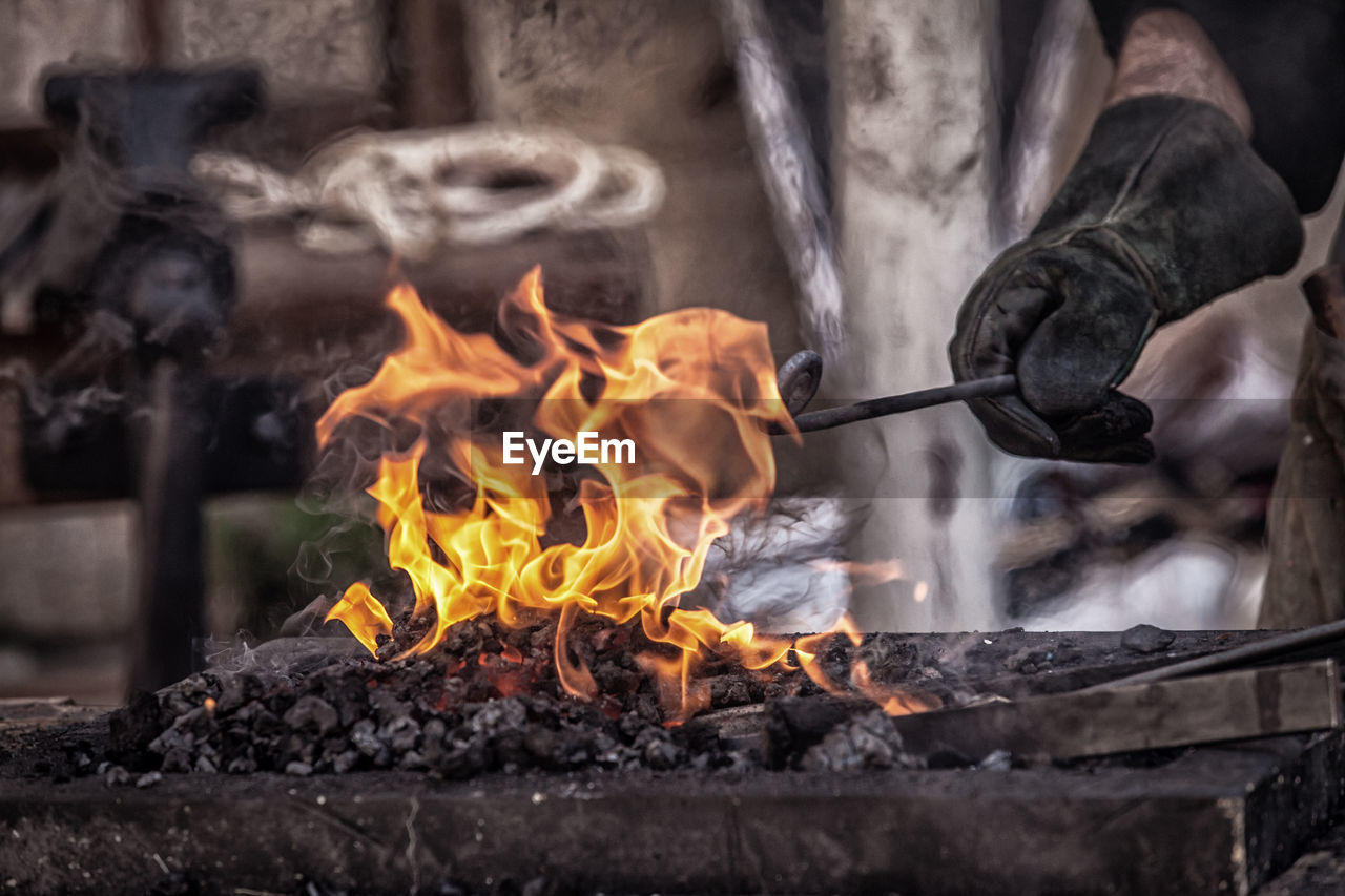 Cropped Hand Holding Metal In Bonfire At Workshop