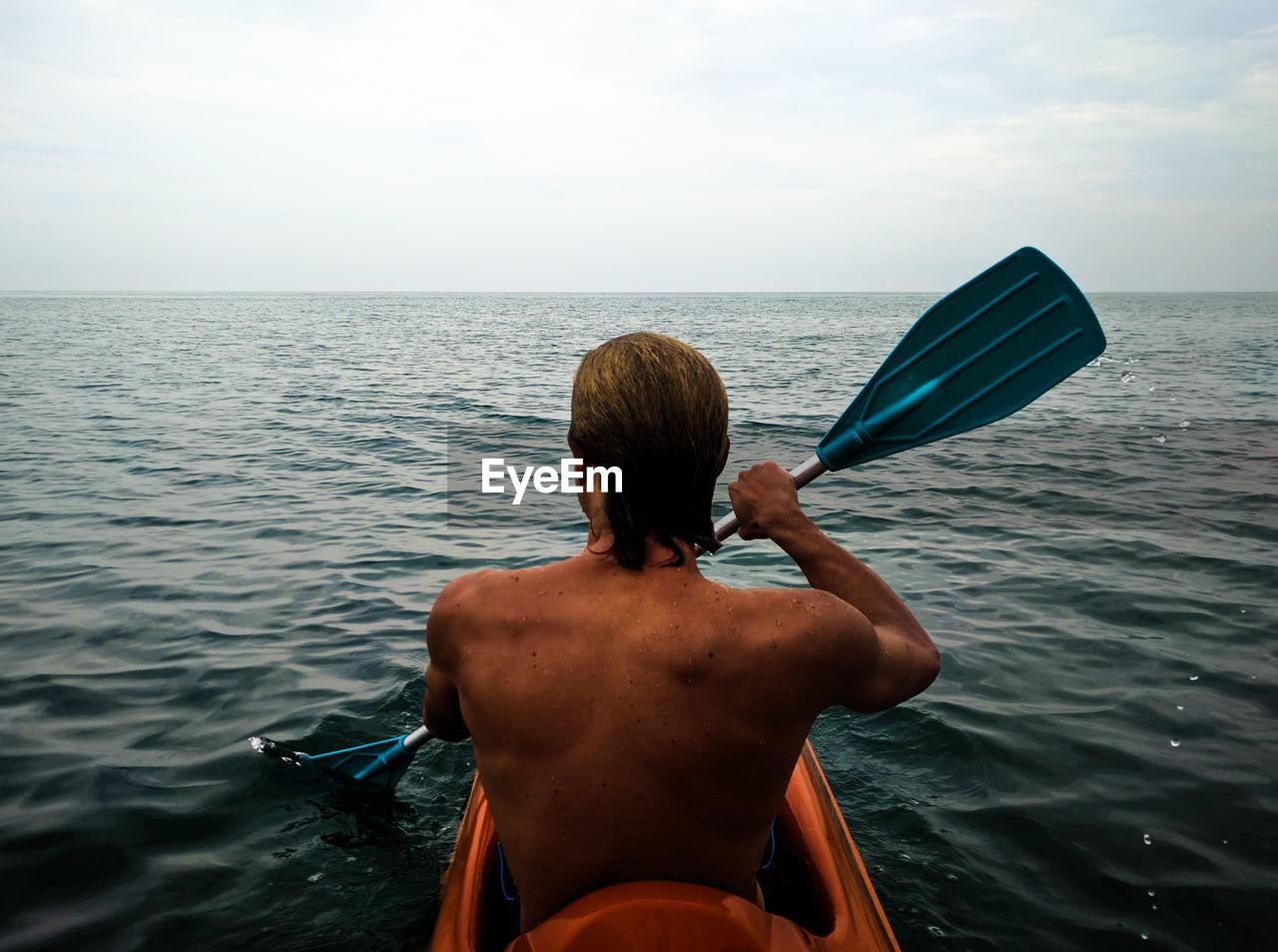 Rear View Of Shirtless Man Kayaking In Sea Against Sky