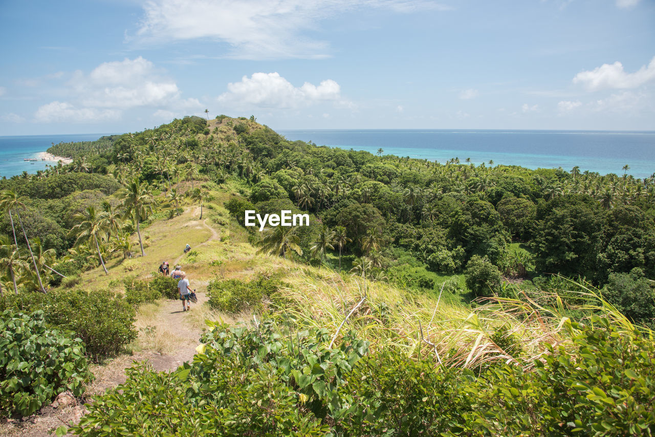 High Angle View Of People Hiking On Green Mountain By Sea