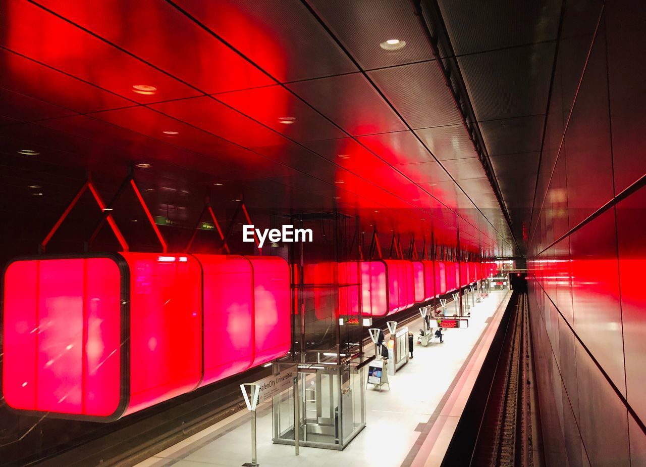 illuminated, transportation, red, indoors, lighting equipment, architecture, mode of transportation, reflection, public transportation, travel, modern, rail transportation, incidental people, in a row, ceiling, built structure, empty, railroad station, seat, diminishing perspective, flooring, electricity, light