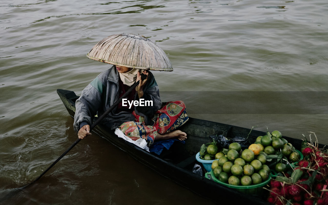 High Angle View Of Woman Paddling Boat With Fruits In Floating Market