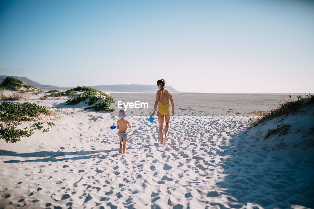 land, beach, real people, sky, two people, togetherness, full length, nature, child, sand, family, childhood, leisure activity, men, rear view, water, people, day, sea, walking, outdoors, son