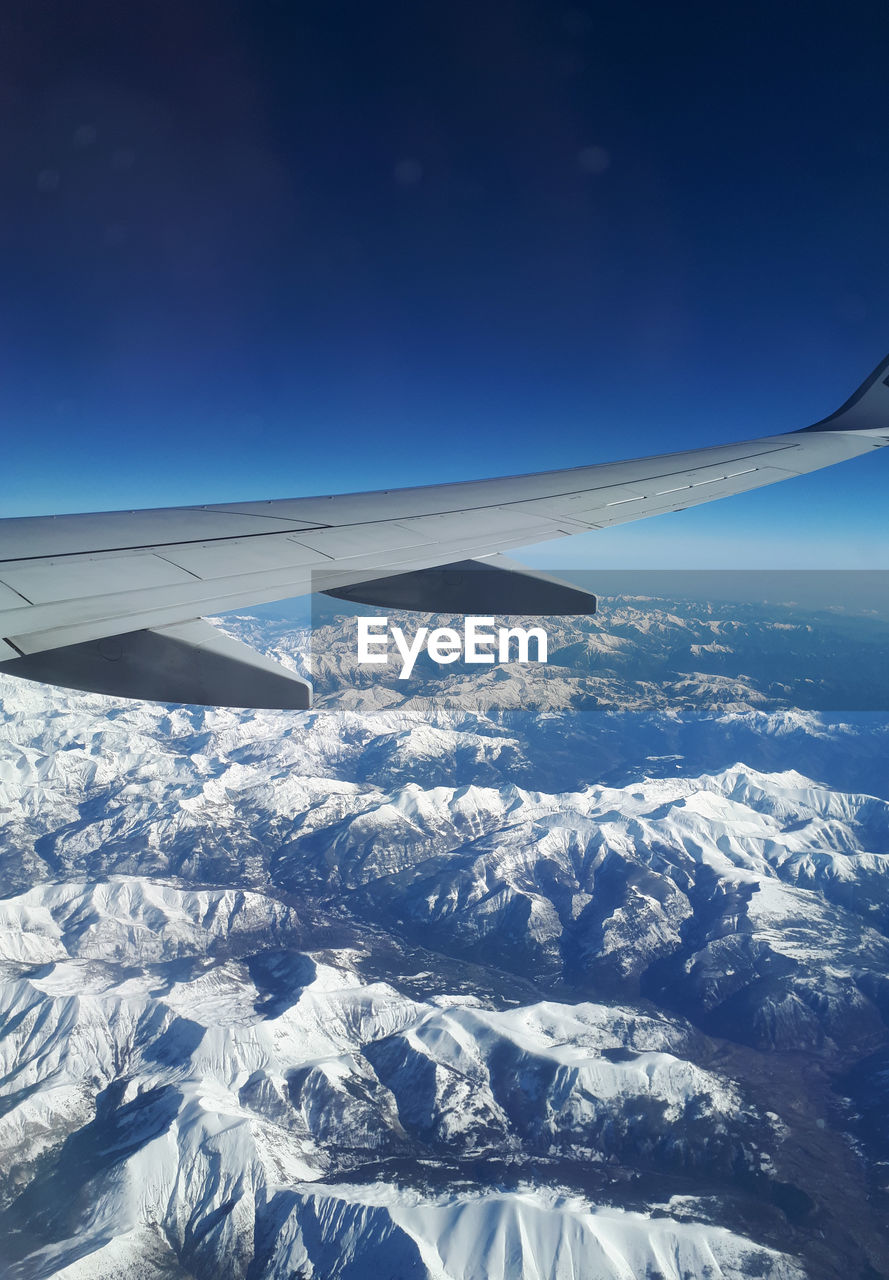 airplane, air vehicle, cold temperature, scenics - nature, snow, winter, beauty in nature, mountain, flying, sky, aircraft wing, transportation, mode of transportation, blue, snowcapped mountain, mid-air, environment, nature, no people, mountain range, outdoors, mountain ridge