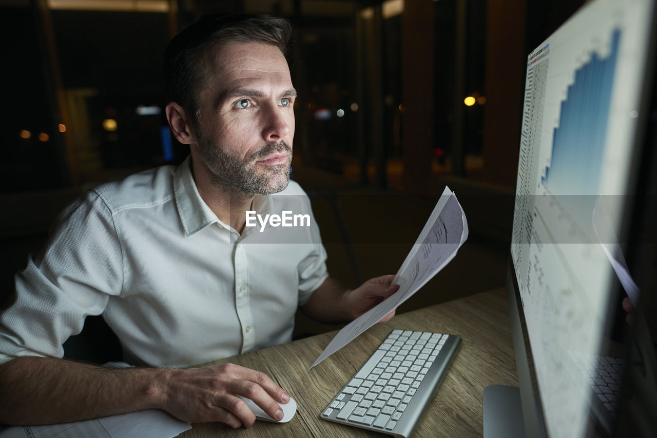 Close-up of businessman using computer in office at night