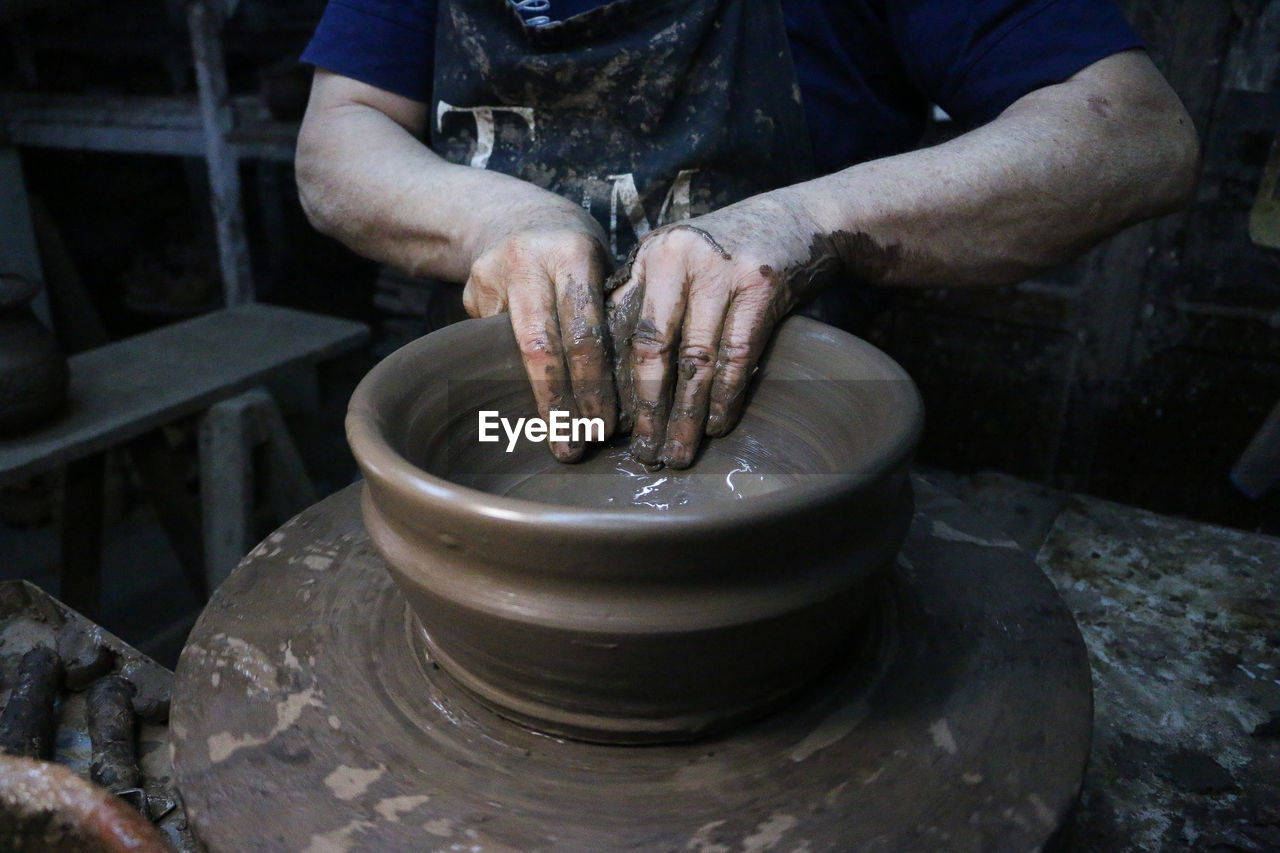 working, occupation, one person, human hand, art and craft, real people, skill, hand, craft, clay, creativity, pottery, preparation, making, expertise, indoors, men, spinning, craftsperson, molding a shape, mud