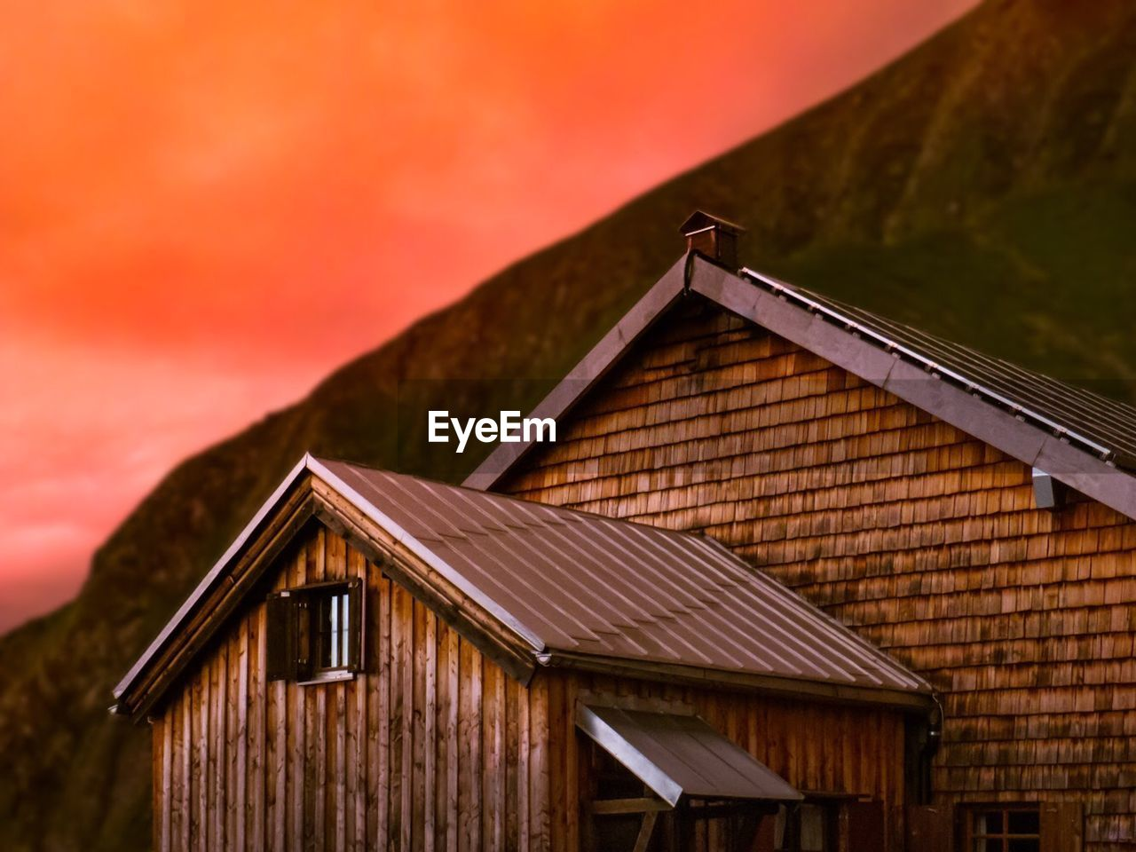 architecture, built structure, building exterior, building, house, sky, sunset, no people, wood - material, nature, roof, outdoors, orange color, mountain, day, focus on foreground, low angle view, beauty in nature, brown, residential district, cottage