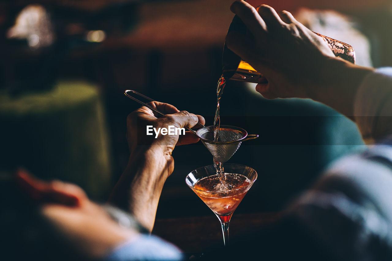 Cropped Image Of Bartender Preparing Cocktail In Bar