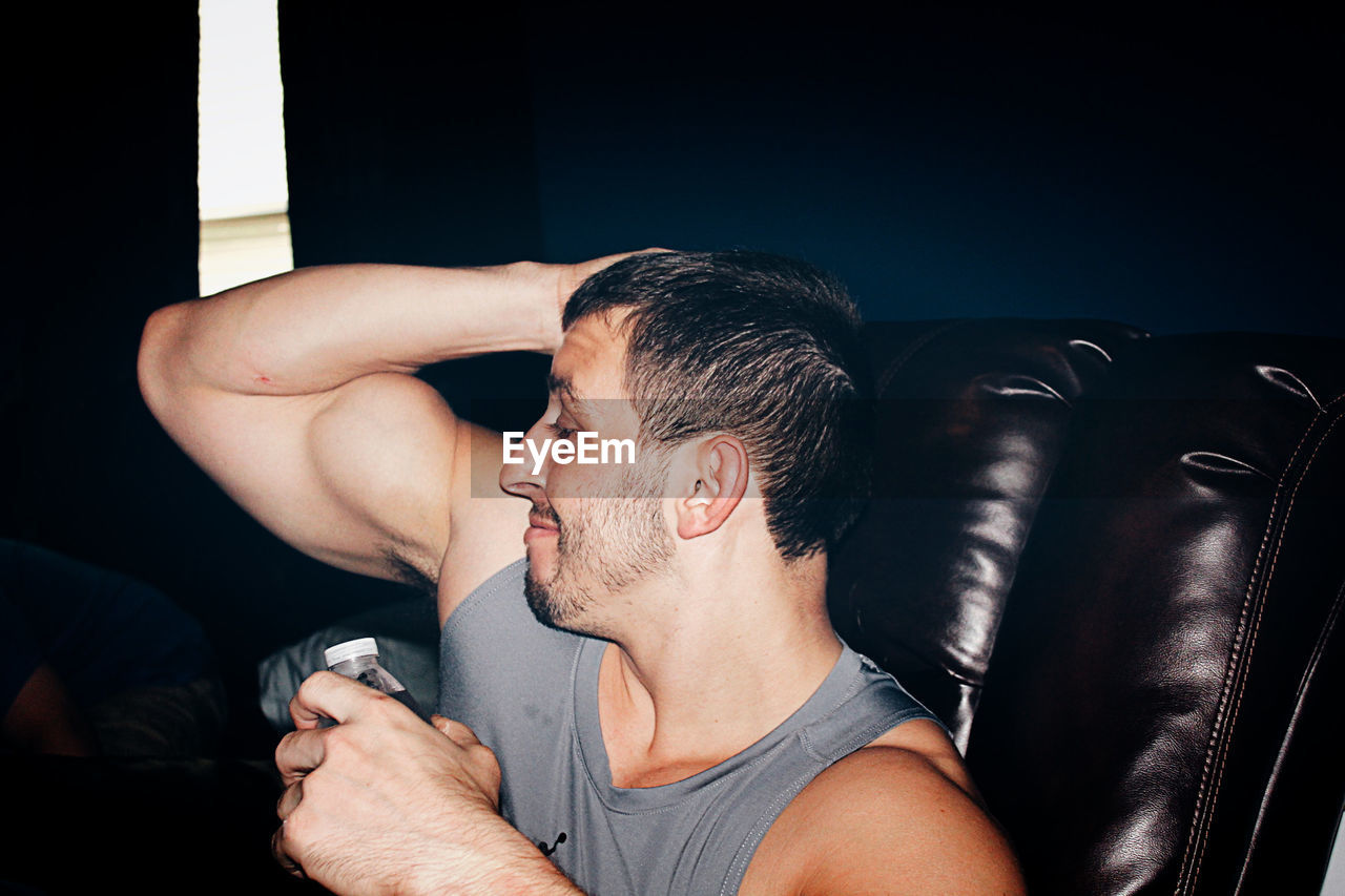 Young Man Showing Biceps While Sitting On Sofa At Home