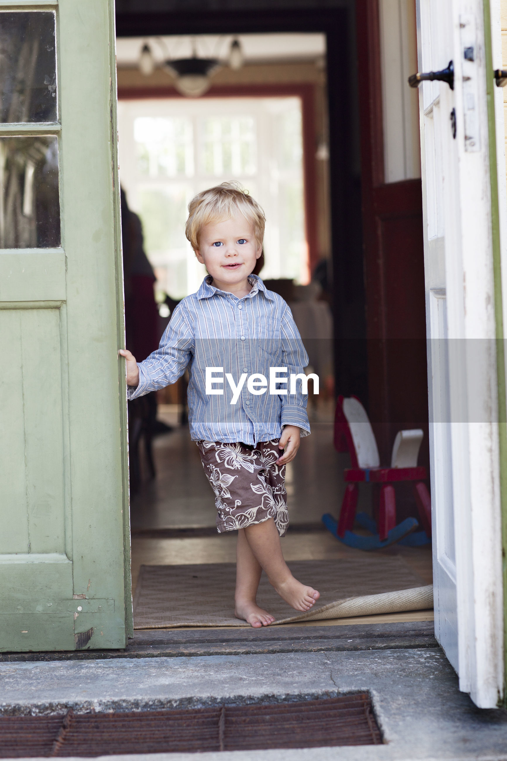 PORTRAIT OF CUTE BOY STANDING BY DOOR