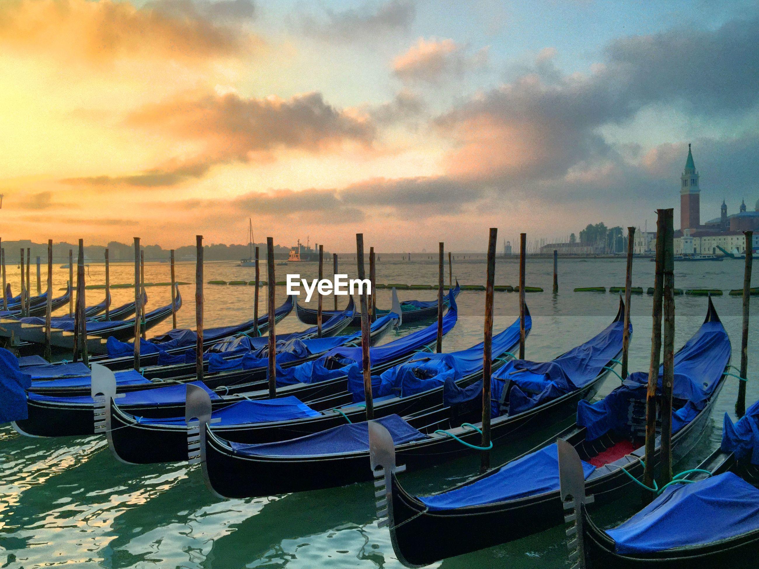 Gondolas moored in lake against sky during sunrise