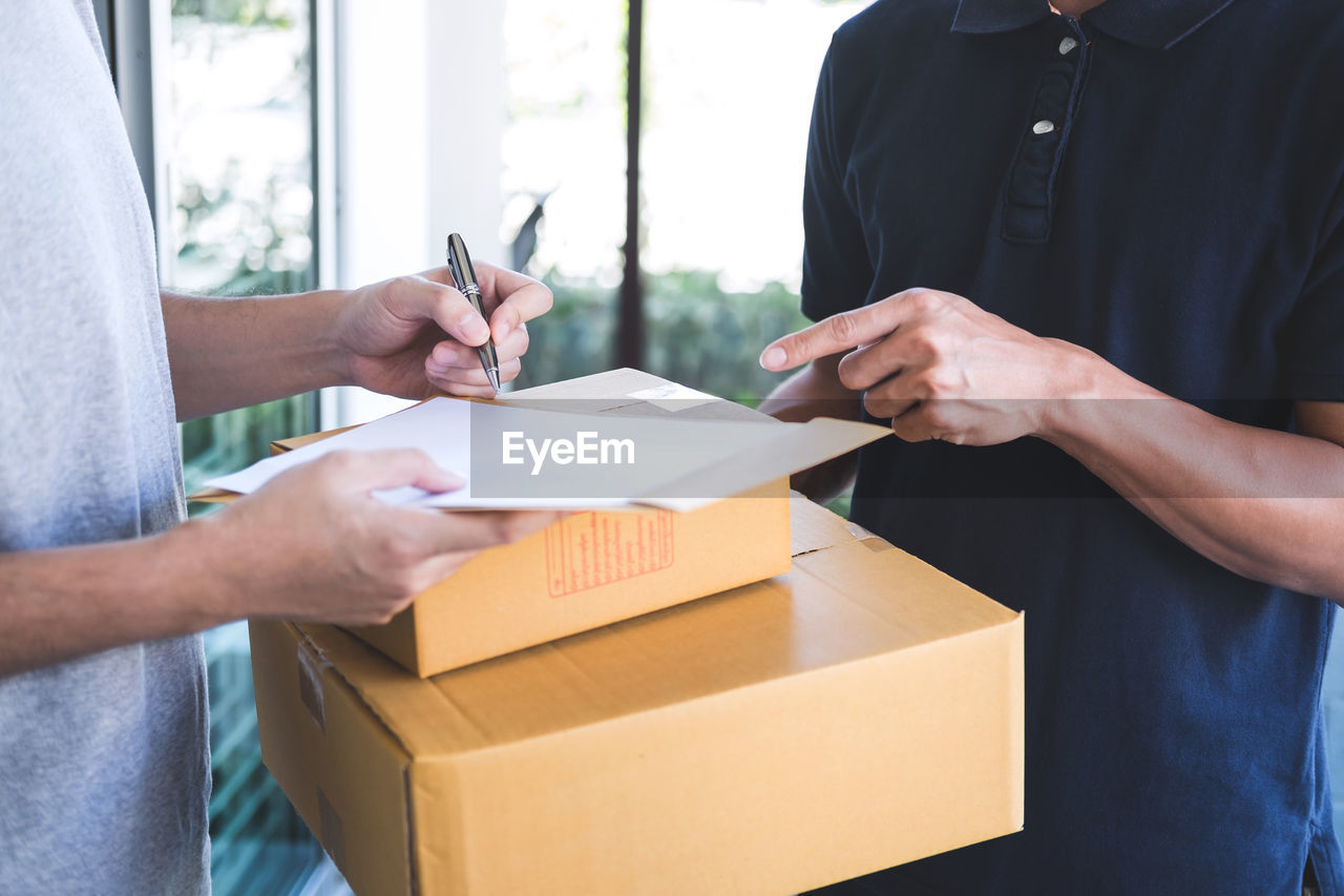 Midsection of man signing while accepting boxes from delivery person