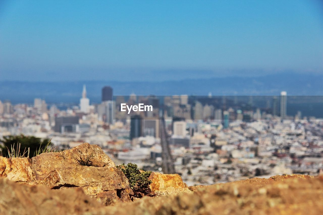 Cityscape with rock in foreground against sky