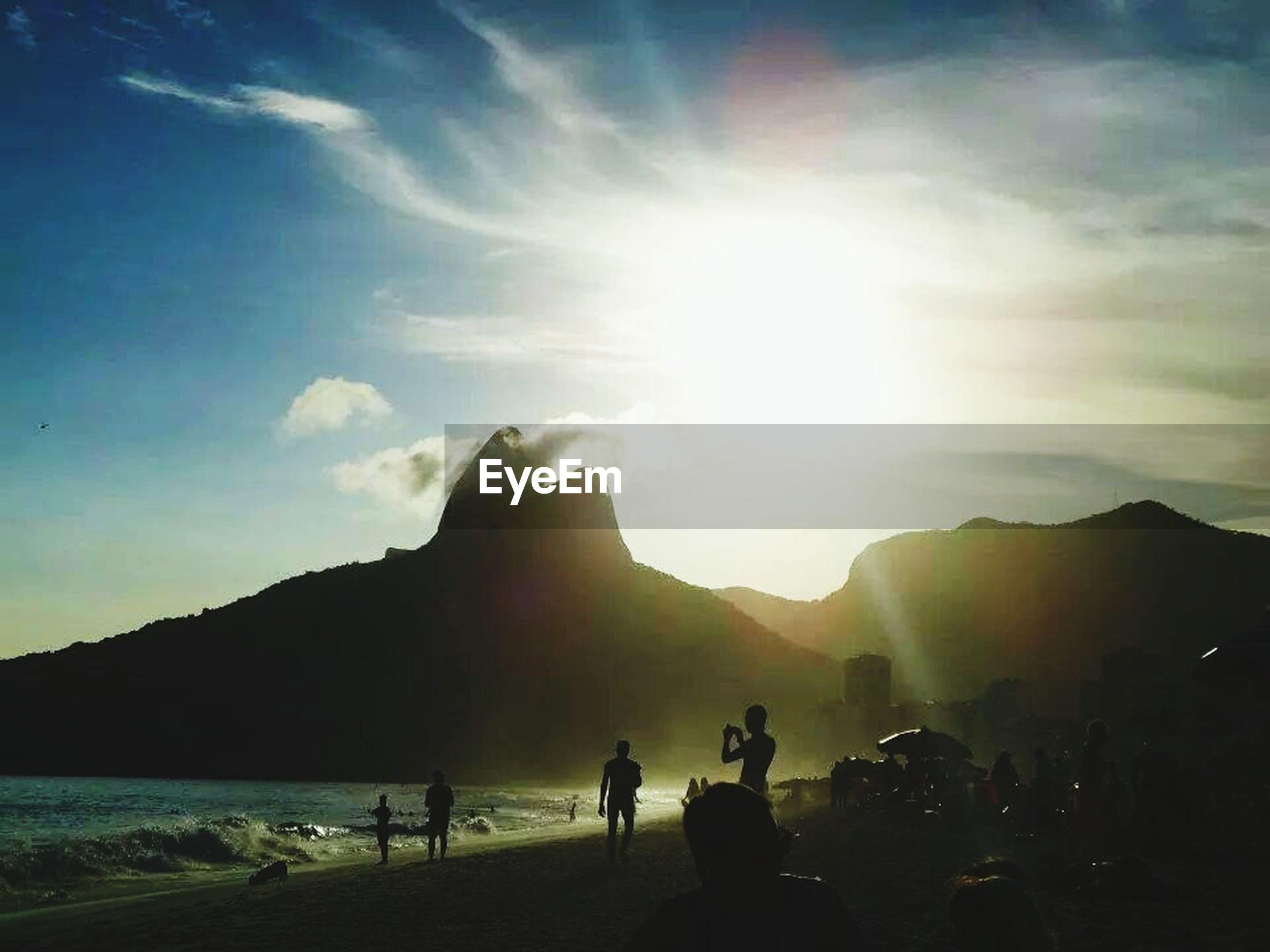 mountain, large group of people, sky, lifestyles, water, sea, leisure activity, sun, men, silhouette, scenics, sunbeam, sunlight, vacations, beach, person, tourist, mountain range, beauty in nature