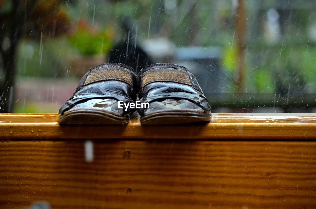 Slipper On Wooden Table During Rainy Season