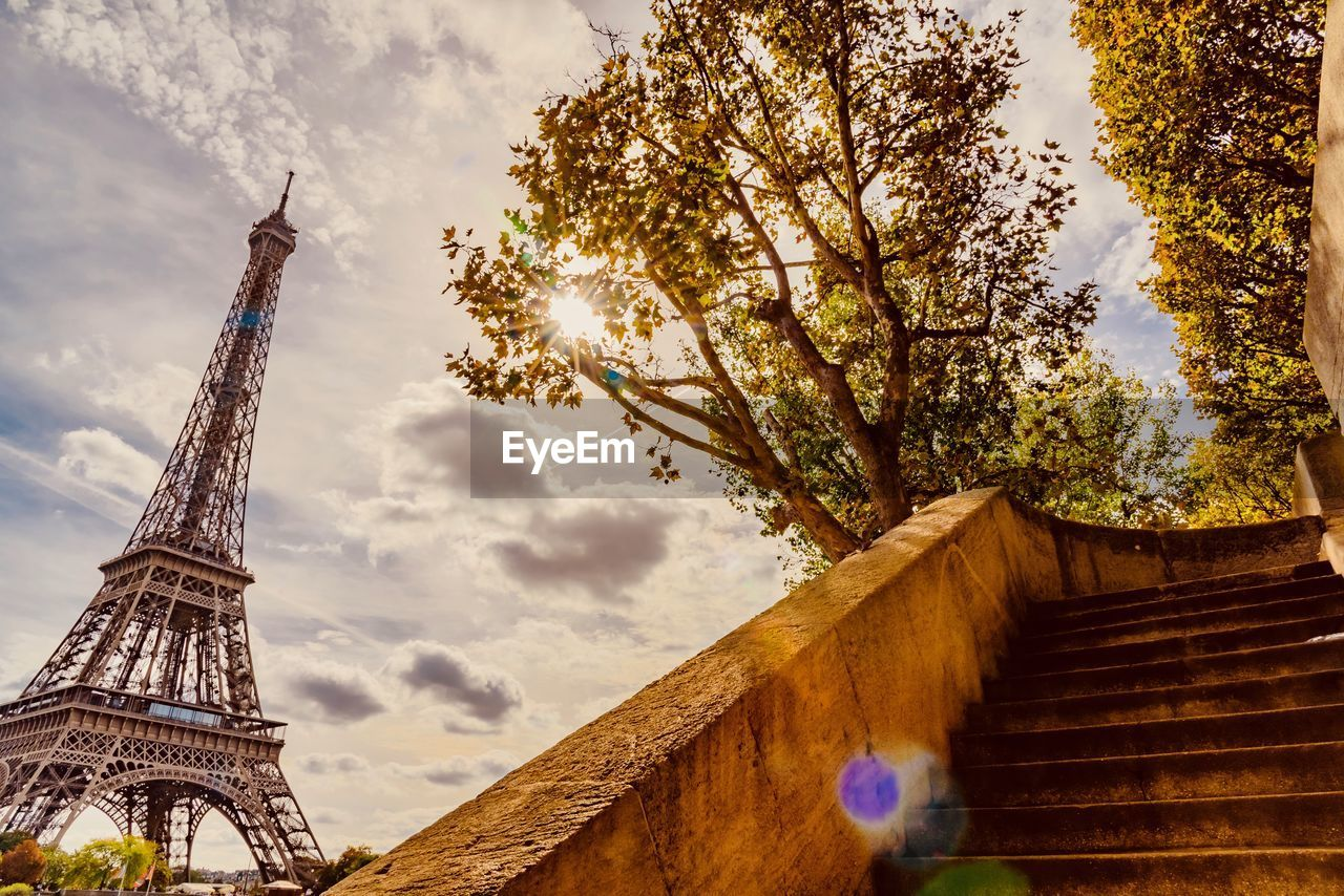 Low angle view of eiffel tower by trees against cloudy sky