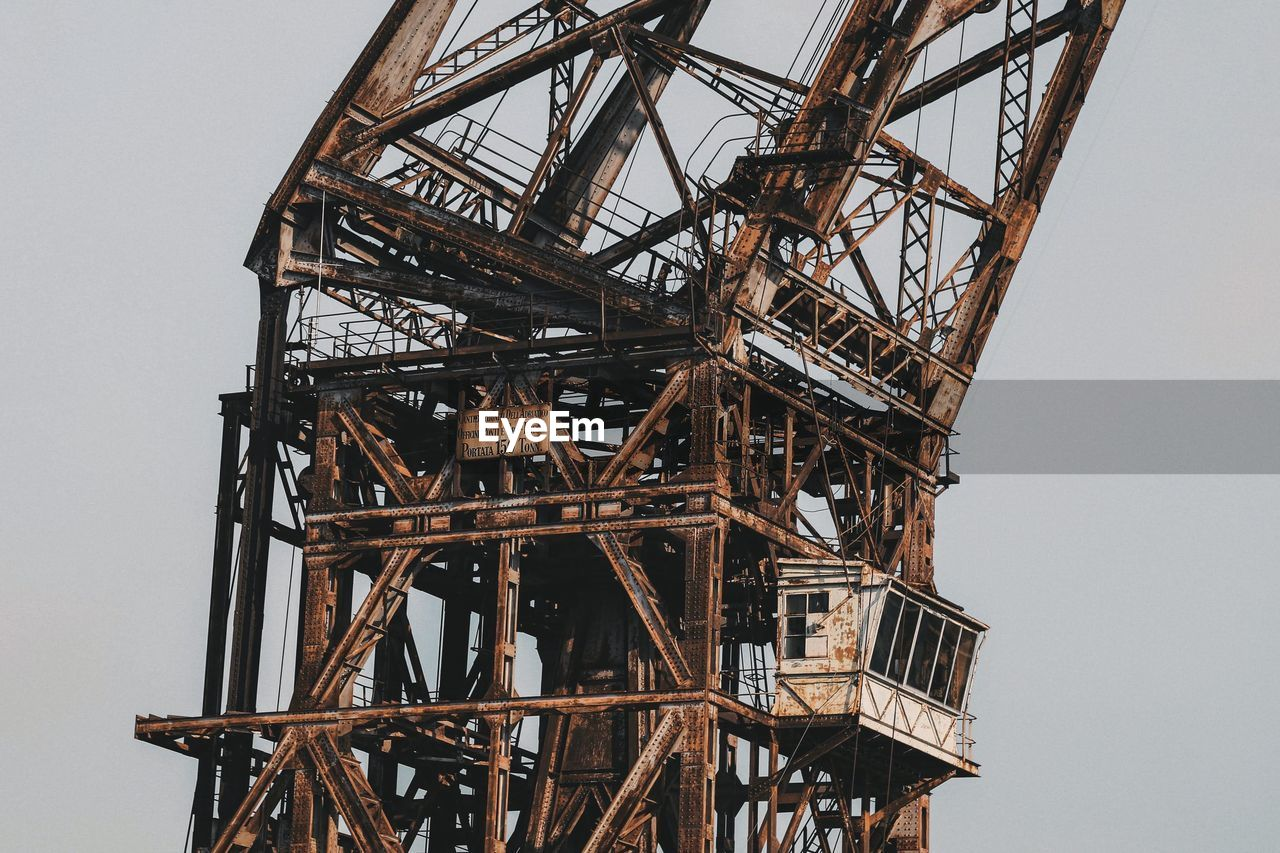 LOW ANGLE VIEW OF OLD CRANE AGAINST SKY