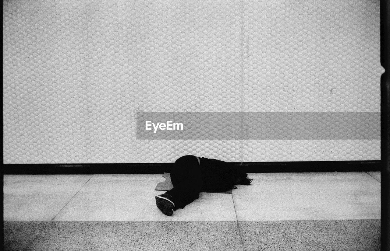 Person lying down on sidewalk against wall