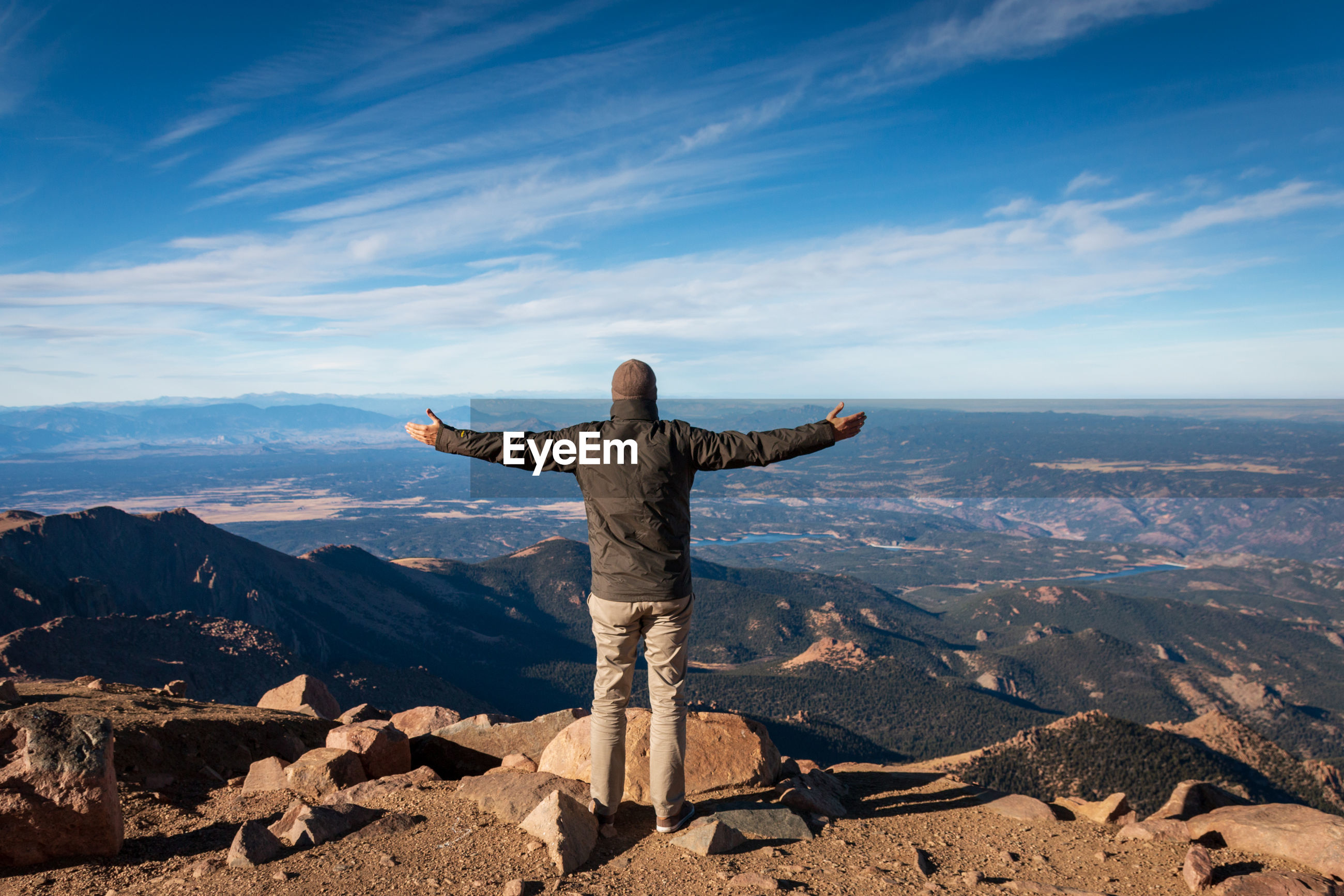 Rear view of man standing on top of pikes peak, colorado with arms wide open against sky