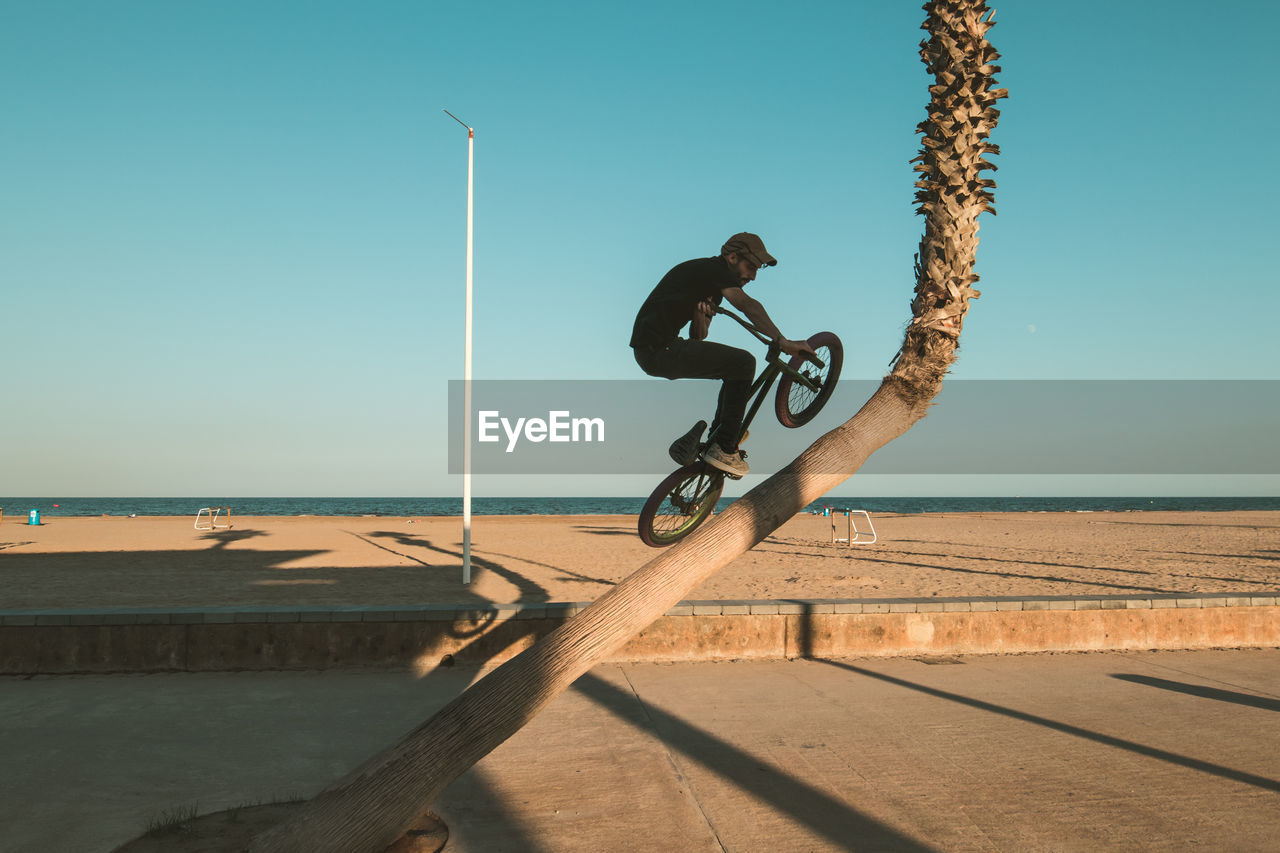Man performing stunt with bicycle against clear sky