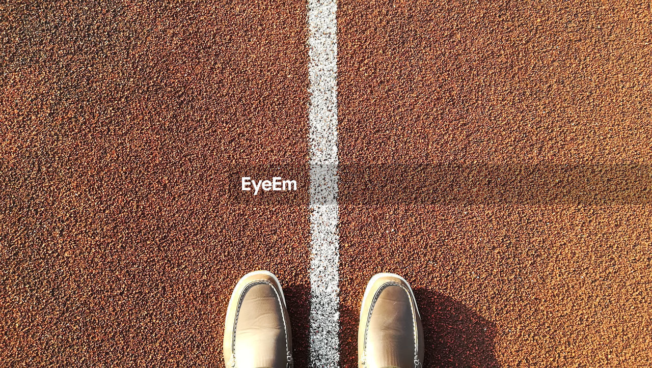 Directly above shot of shoes on running track
