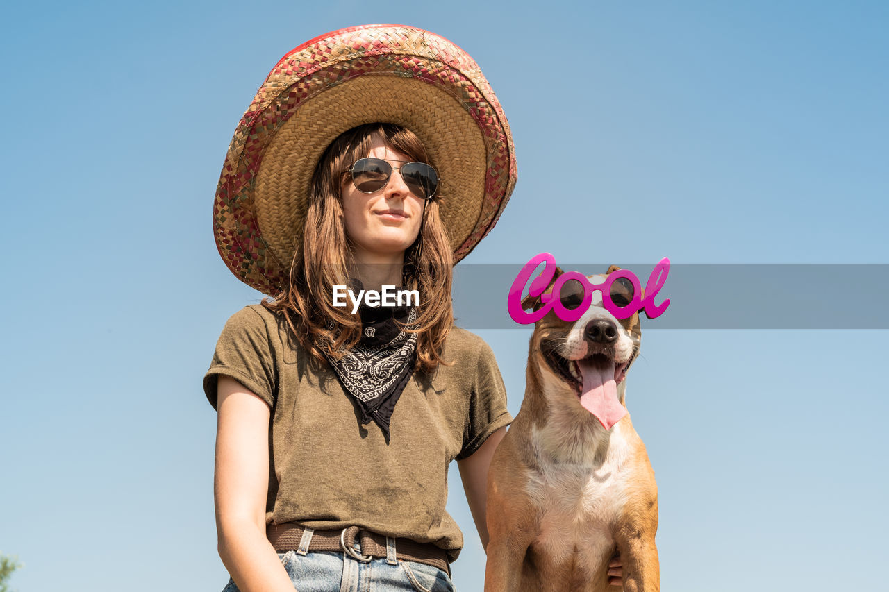 Low Angle View Of Young Woman Wearing Cowboy Hat While Standing With Dog Against Clear Sky