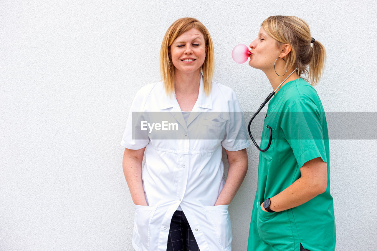 Nurse blowing bubble gum by doctor against wall