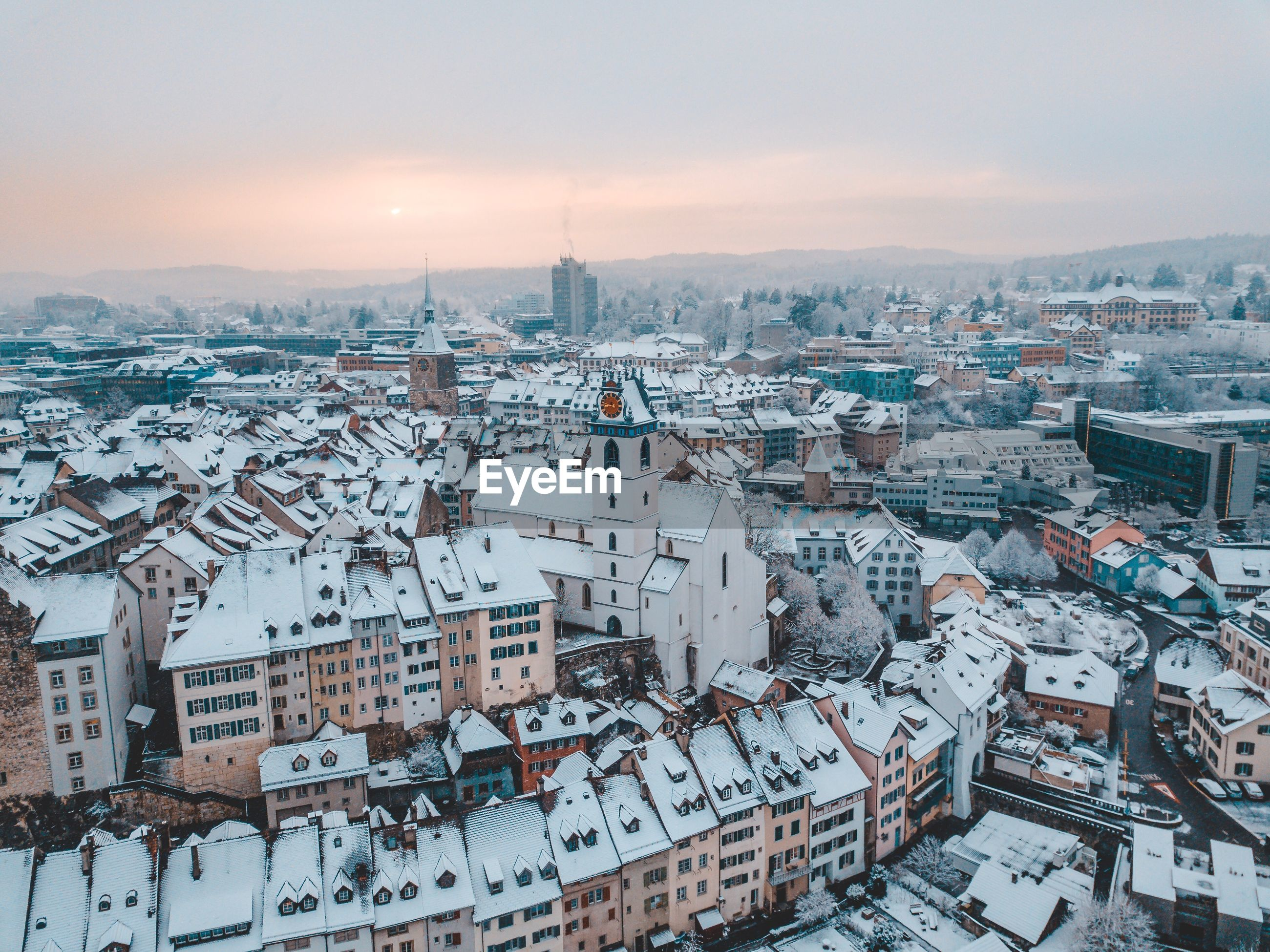 Aerial view of snow covered townscape against sky at sunset