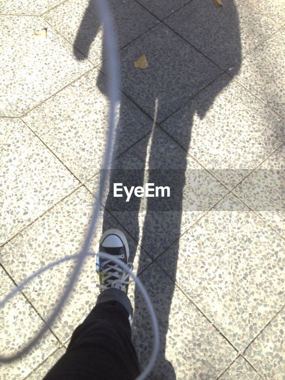 shadow, sunlight, low section, high angle view, one person, human body part, focus on shadow, day, standing, human leg, outdoors, street, leisure activity, lifestyles, real people, people, one man only, adult, close-up, adults only