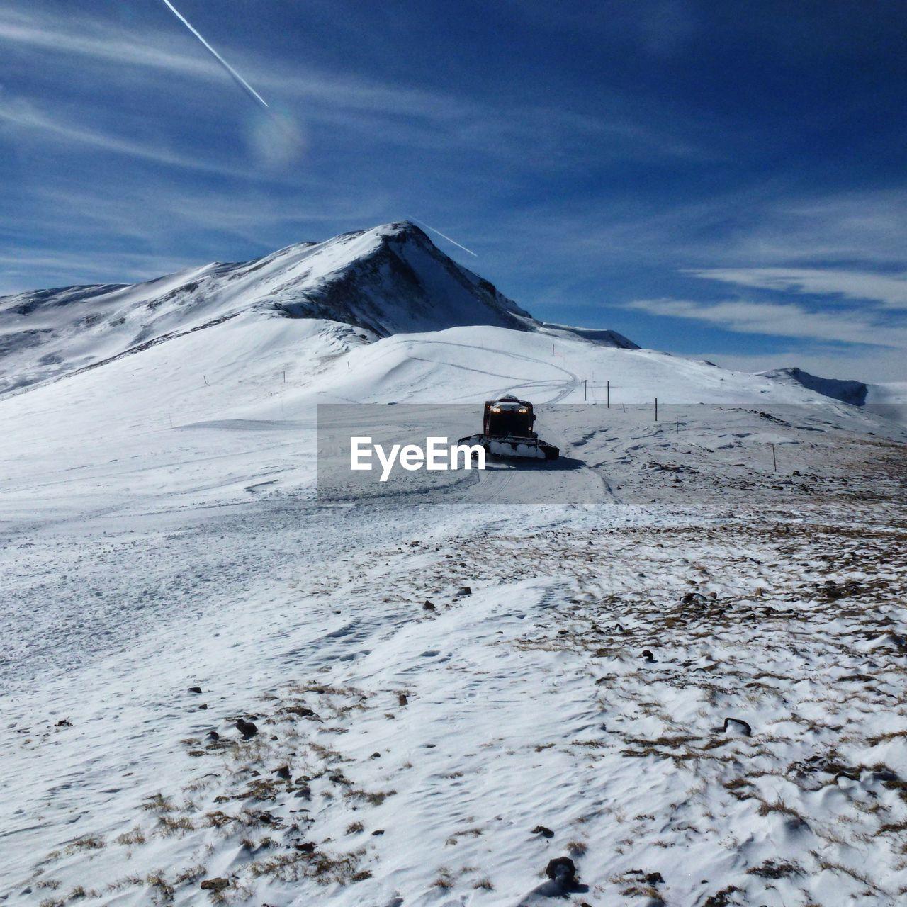 Snow Groomer On Snowcapped Mountain Against Sky