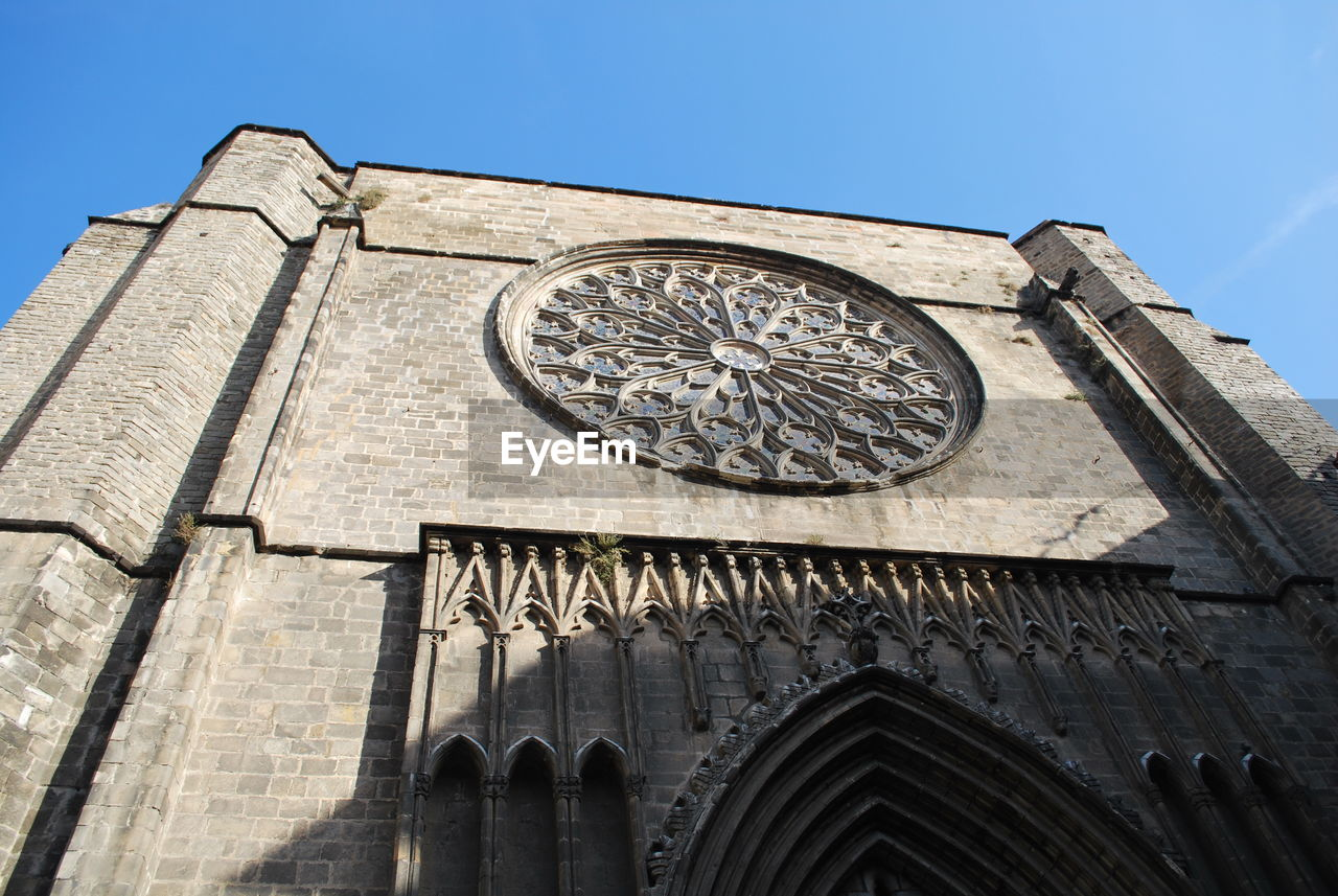 low angle view, architecture, building exterior, built structure, religion, place of worship, spirituality, rose window, outdoors, day, history, travel destinations, facade, no people, sky, clear sky