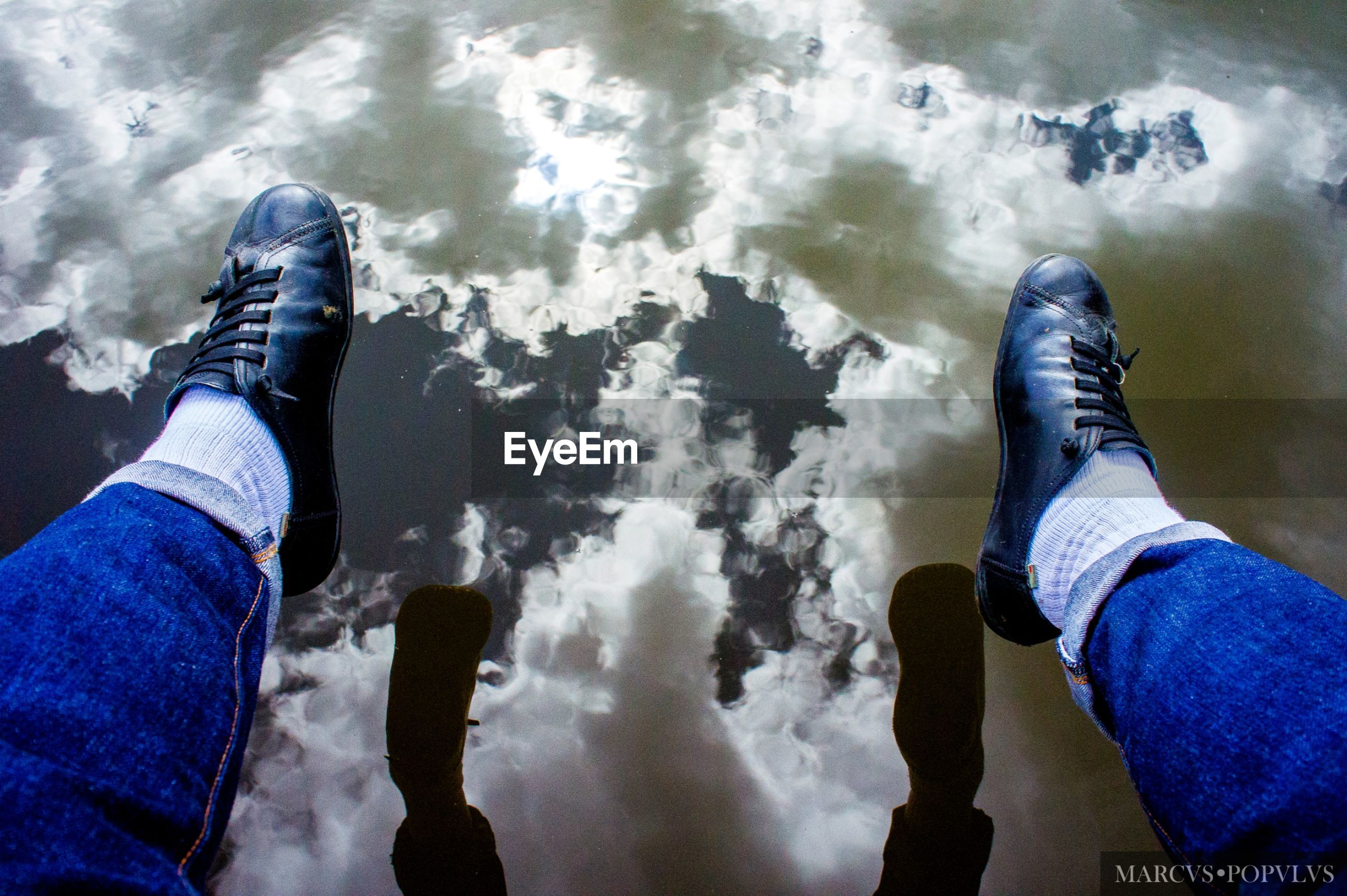 low section, human body part, personal perspective, human leg, real people, body part, jeans, people, nature, two people, lifestyles, togetherness, leisure activity, shoe, high angle view, day, men, cloud - sky, water, outdoors, human foot