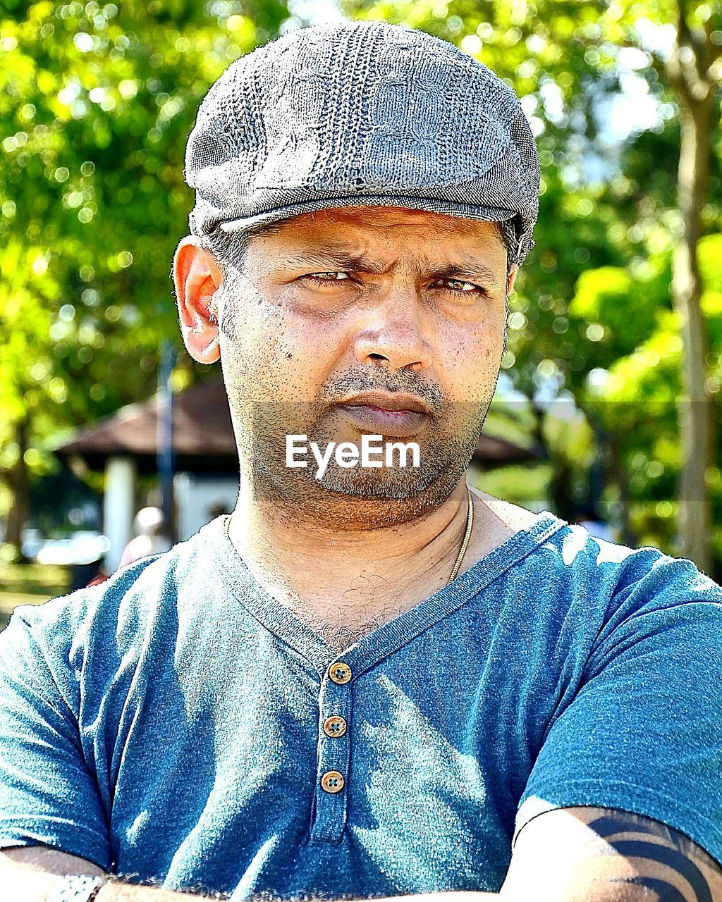 one person, looking at camera, outdoors, portrait, headshot, day, casual clothing, real people, flat cap, cap, focus on foreground, leisure activity, lifestyles, close-up, tree, one man only, only men, adults only, people, adult