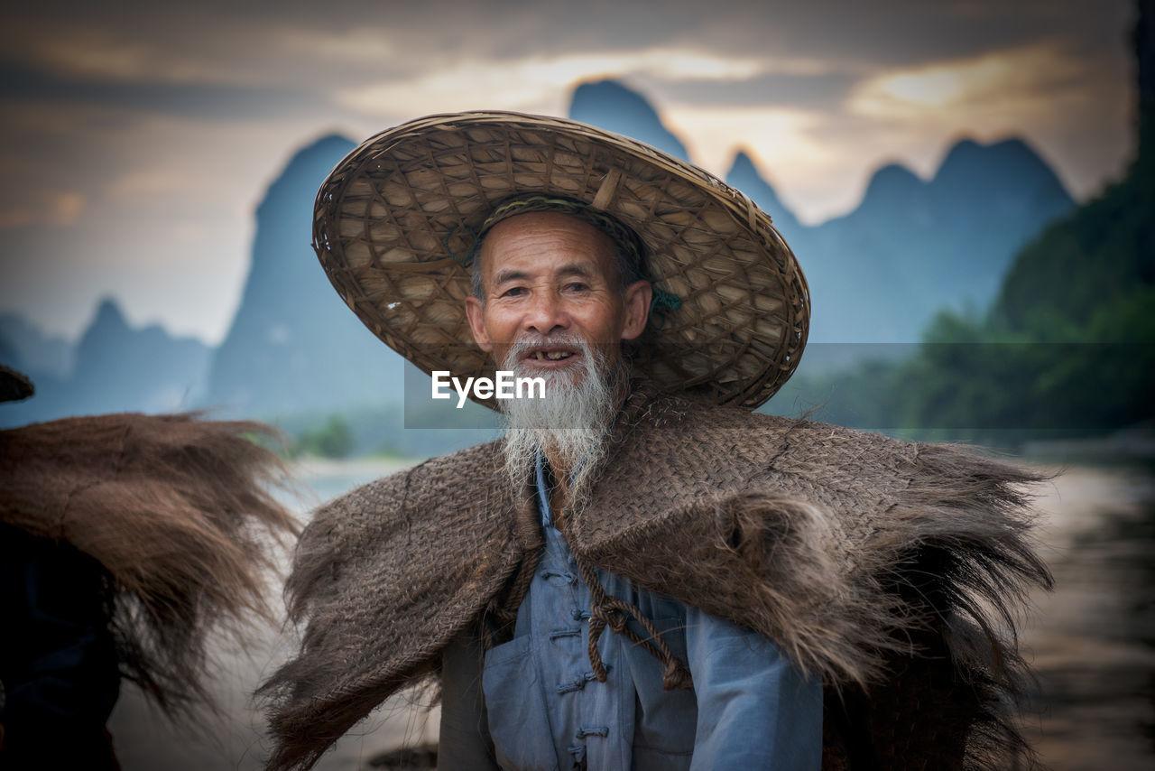 Portrait of smiling senior man wearing hat during sunset