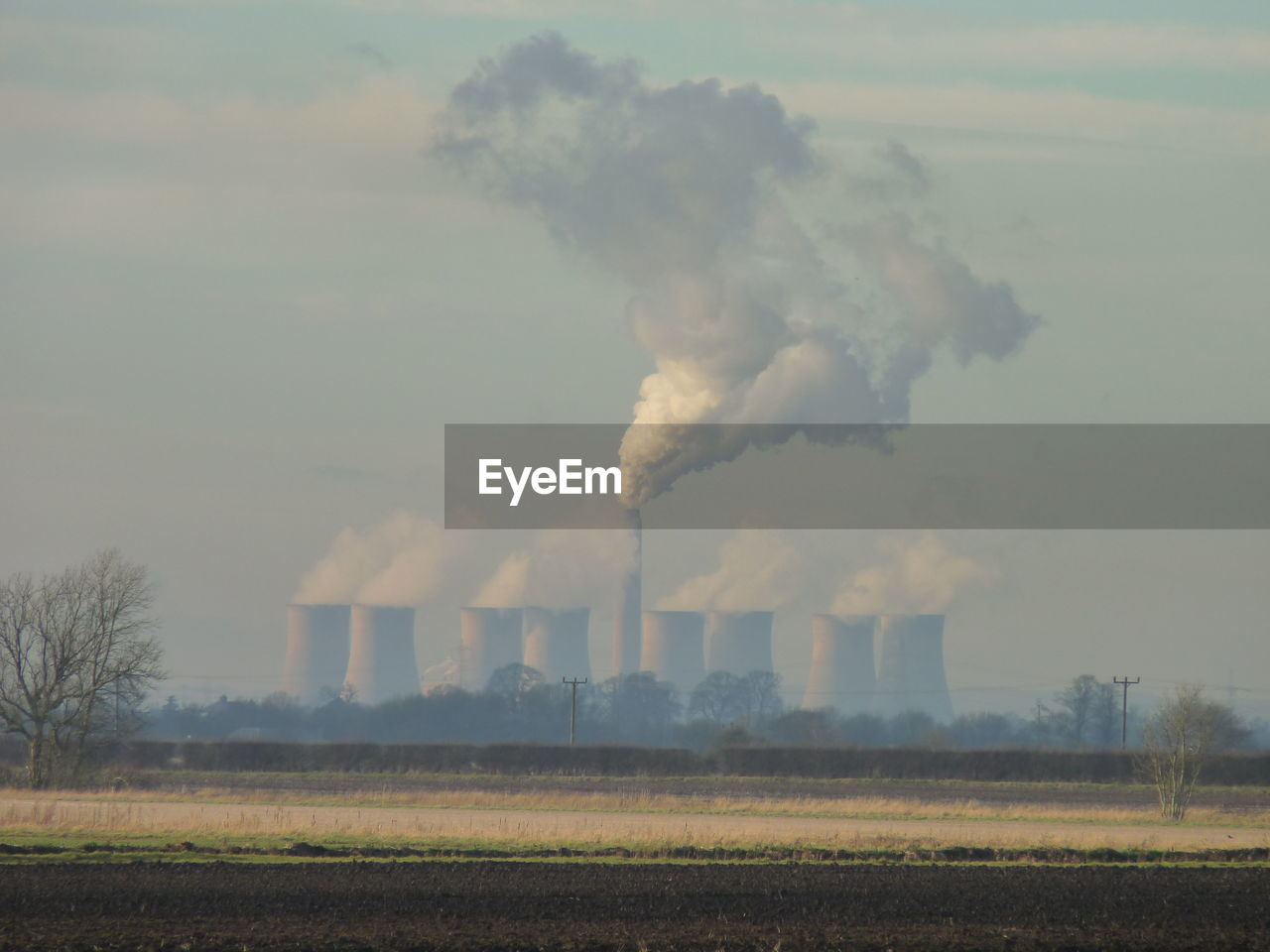 environment, smoke - physical structure, environmental issues, pollution, air pollution, emitting, smoke stack, nature, sky, factory, field, industry, land, smoke, day, building exterior, outdoors, environmental damage, no people, chimney, fumes, atmospheric, ecosystem, cooling tower