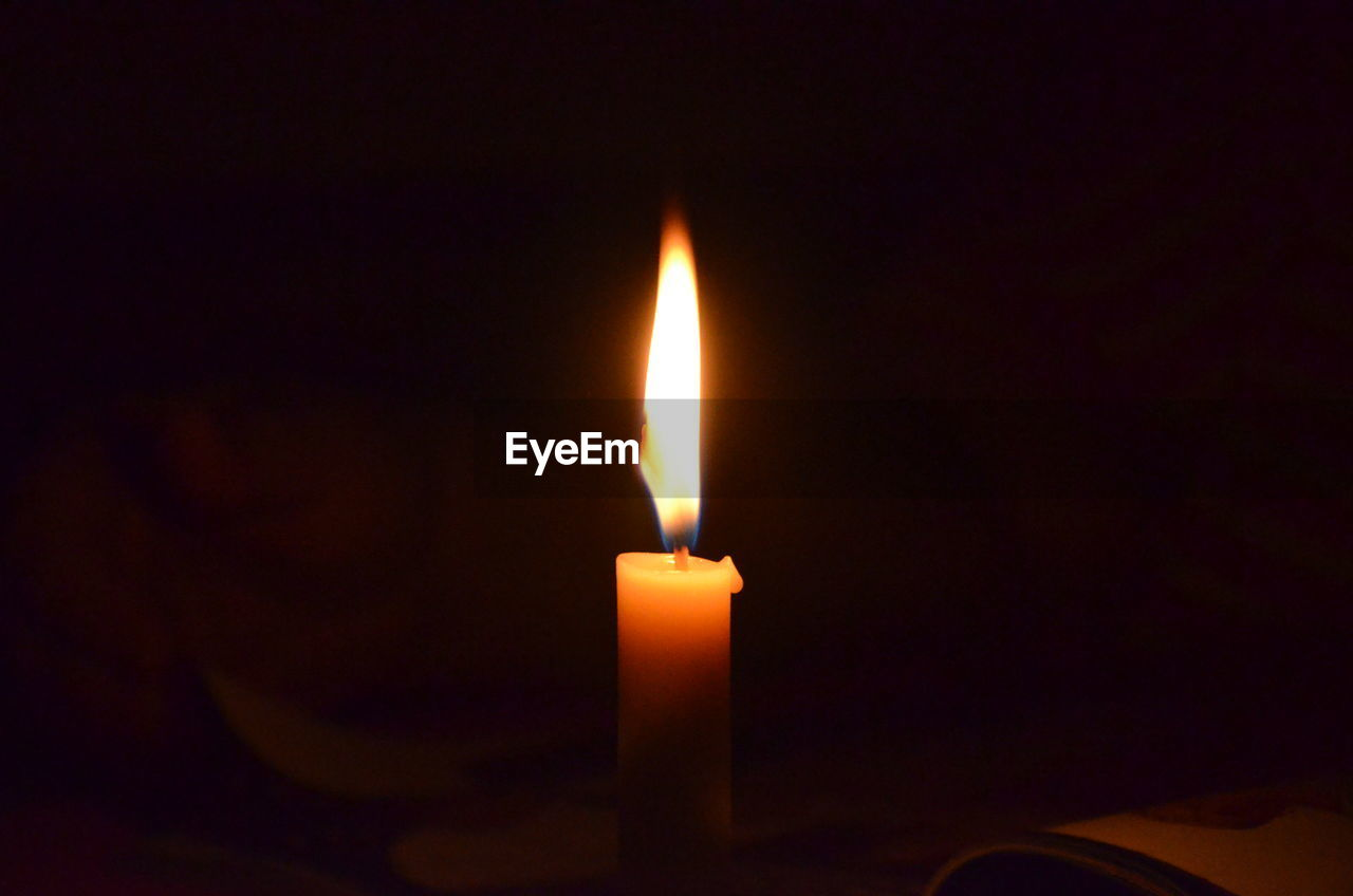 Close-Up Of Candle Burning In Dark Room