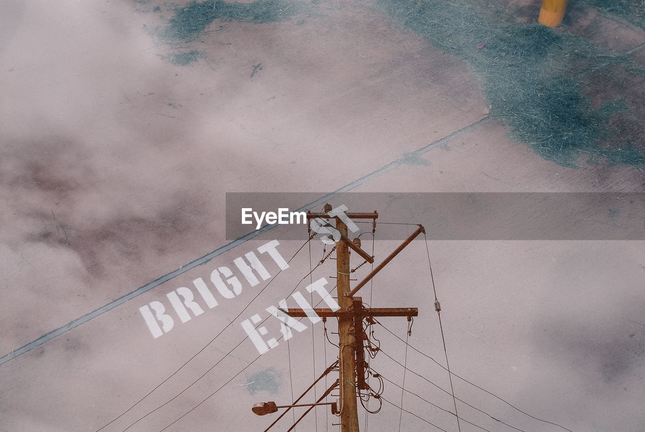 day, low angle view, no people, nature, communication, sky, technology, connection, architecture, outdoors, cloud - sky, built structure, cable, metal, power line, text, electricity, sign, western script, pole, power supply, construction equipment
