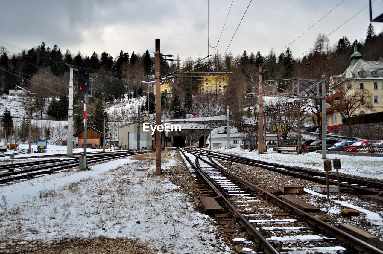 rail transportation, snow, cold temperature, winter, railroad track, track, transportation, tree, sky, nature, mode of transportation, no people, plant, built structure, architecture, public transportation, covering, building exterior, day, outdoors, snowcapped mountain