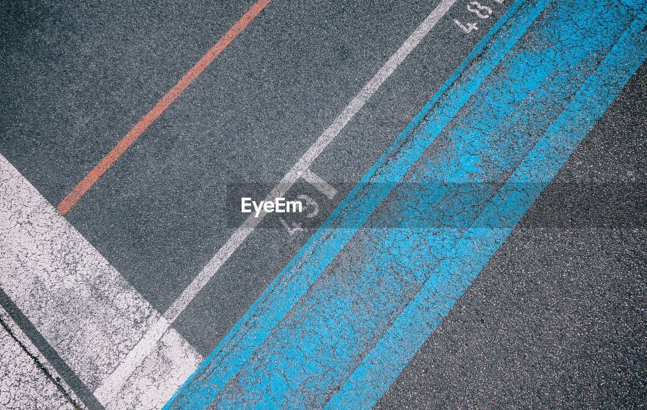high angle view, day, no people, road, sport, running track, marking, road marking, full frame, competition, outdoors, asphalt, pattern, track and field, symbol, blue, competitive sport, sign, close-up, transportation, dividing line