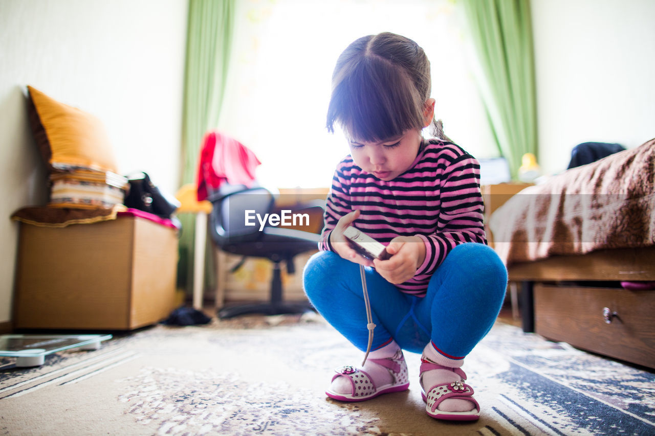 Cute girl holding camera while crouching at home