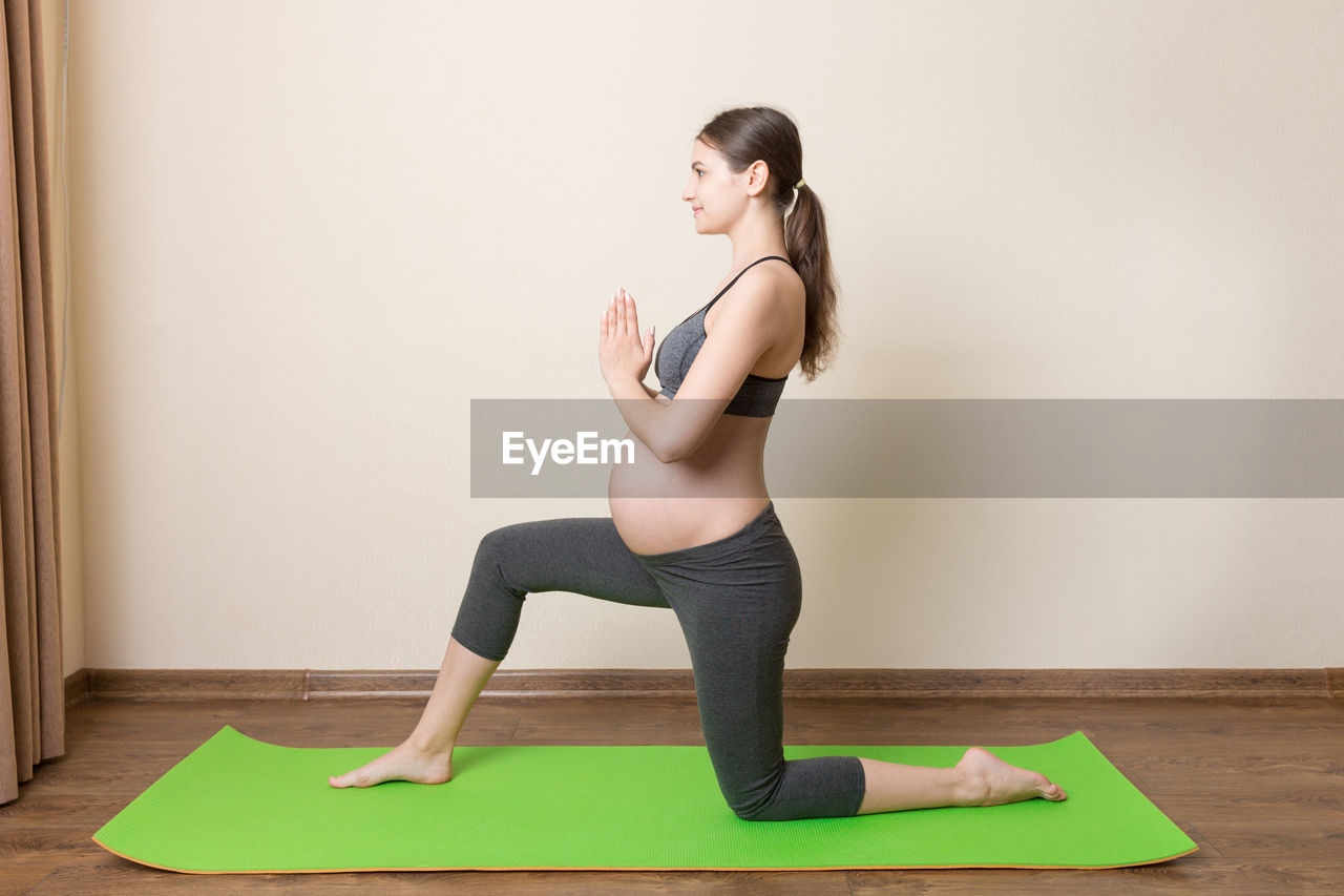 SIDE VIEW OF WOMAN SITTING AGAINST WALL
