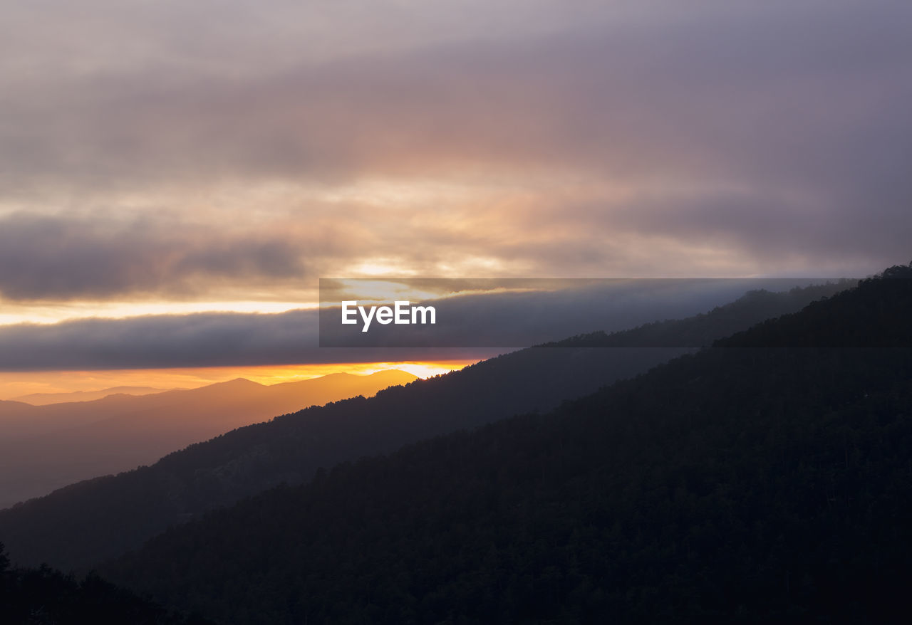 sky, beauty in nature, sunset, cloud - sky, tranquility, scenics - nature, tranquil scene, mountain, idyllic, non-urban scene, nature, no people, silhouette, orange color, environment, mountain range, landscape, outdoors, remote, hazy