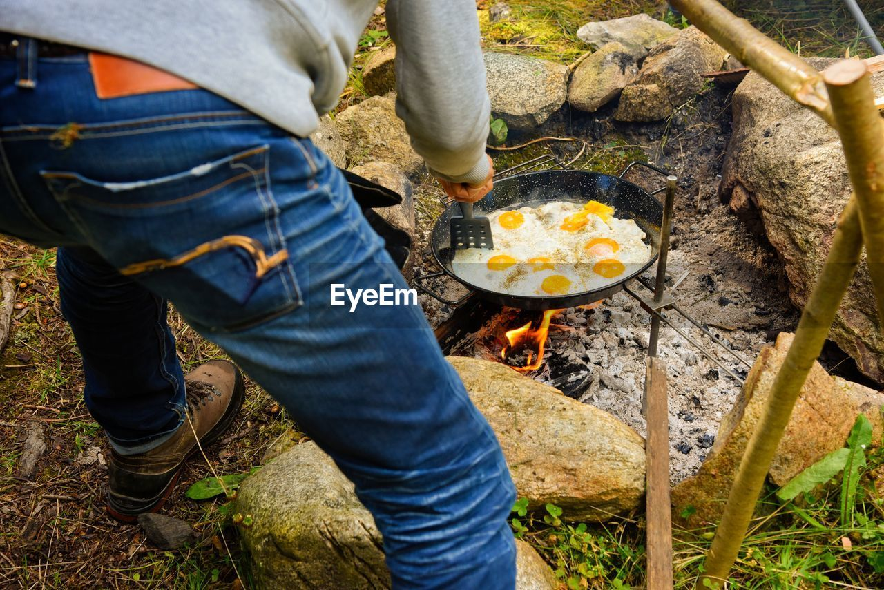 burning, fire, heat - temperature, flame, fire - natural phenomenon, food, low section, food and drink, men, nature, one person, real people, preparation, kitchen utensil, day, casual clothing, preparing food, standing, household equipment, jeans, outdoors, wood, bonfire, camping stove