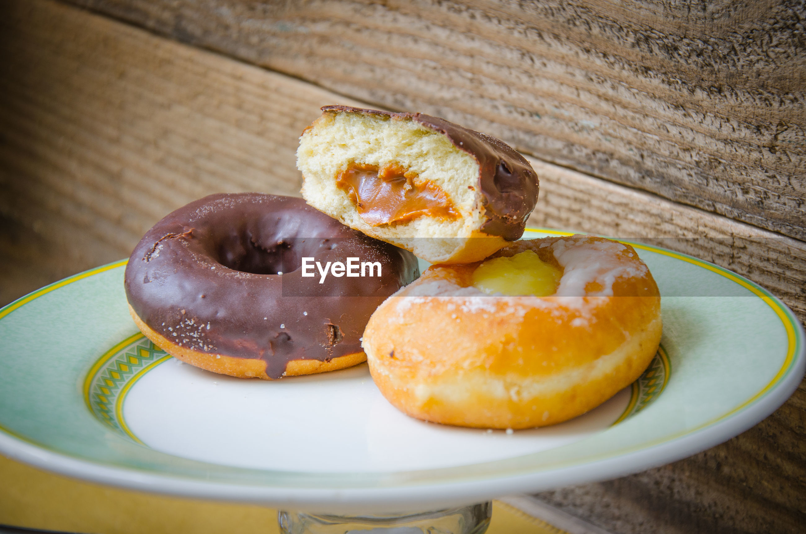 Close-up of donuts in plate on wooden table