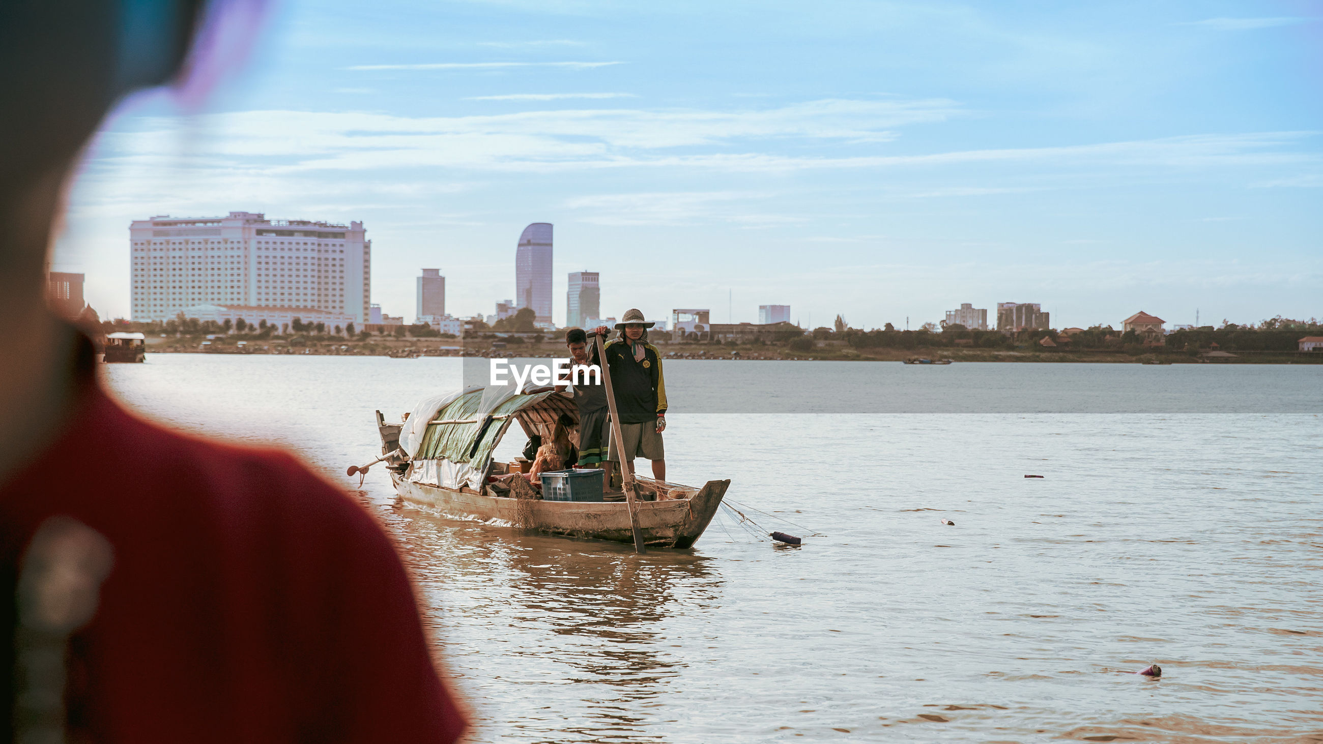 People in wooden boat on river against sky