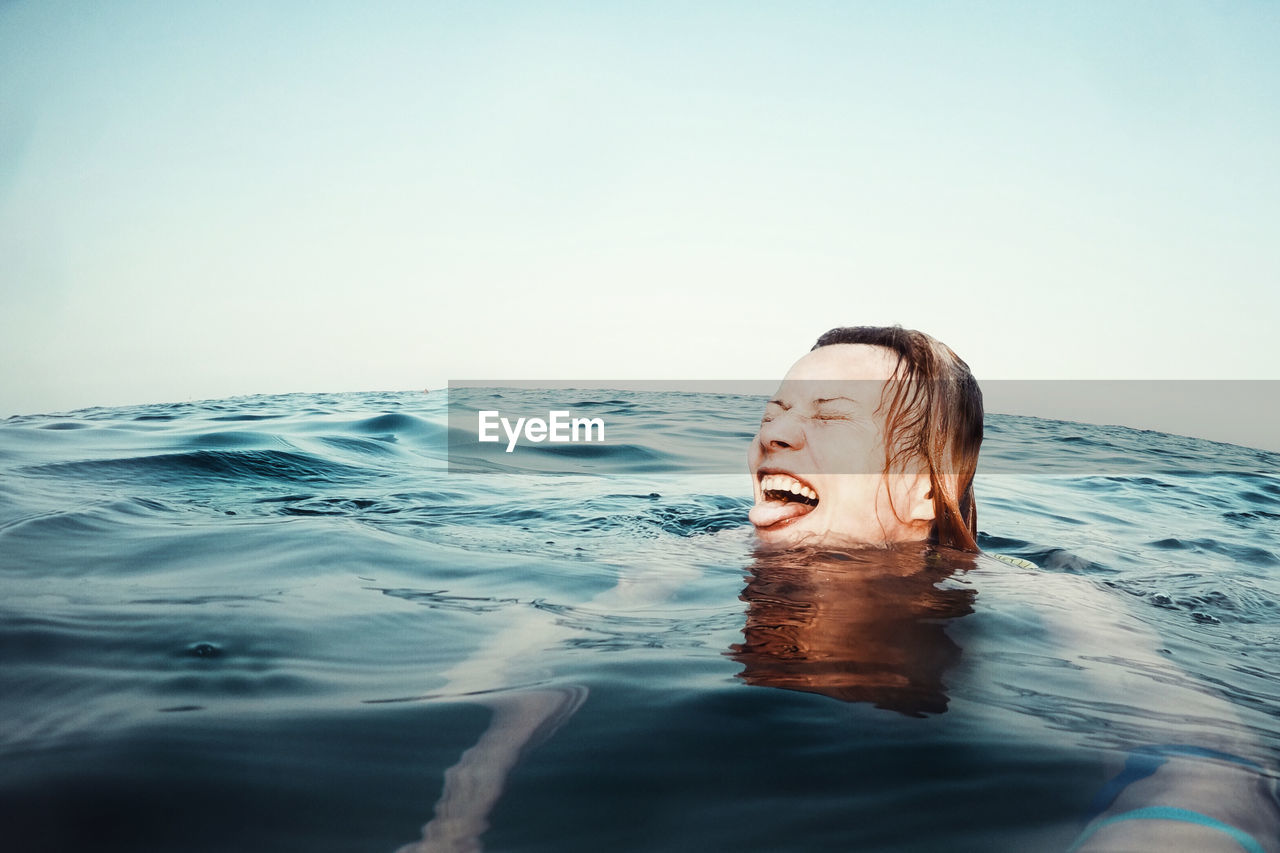 Young Woman Swimming In Sea Against Sky